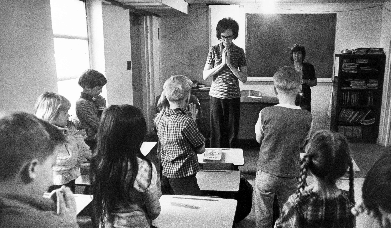 Volunteer classroom aid Rose Snuffler leads a prayer for students at Faith Gospel Tabernacle Elementary School