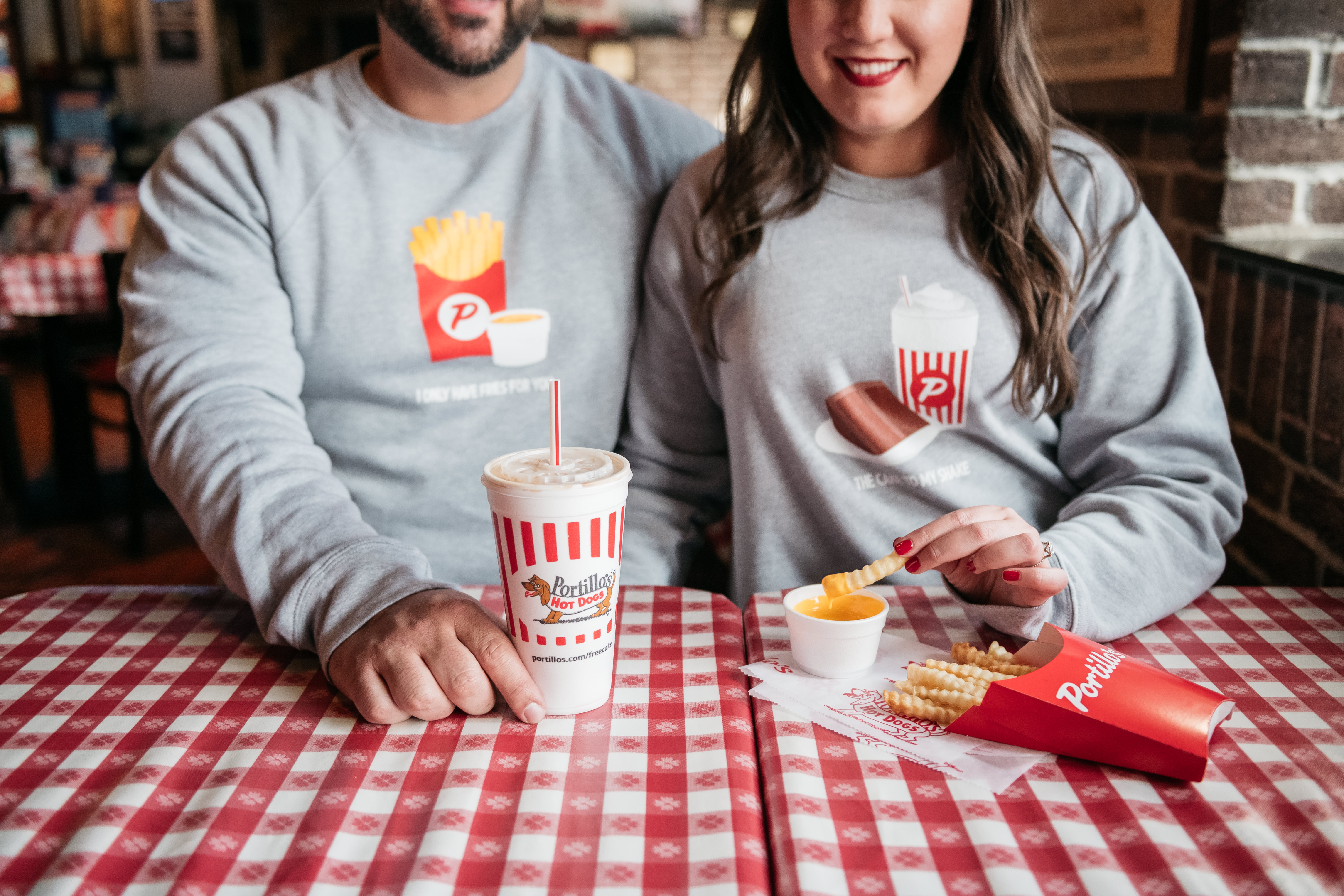 A white man and white woman sit next to each other at a table covered with a checkered cloth. They hold a container of fries and a soda cup.