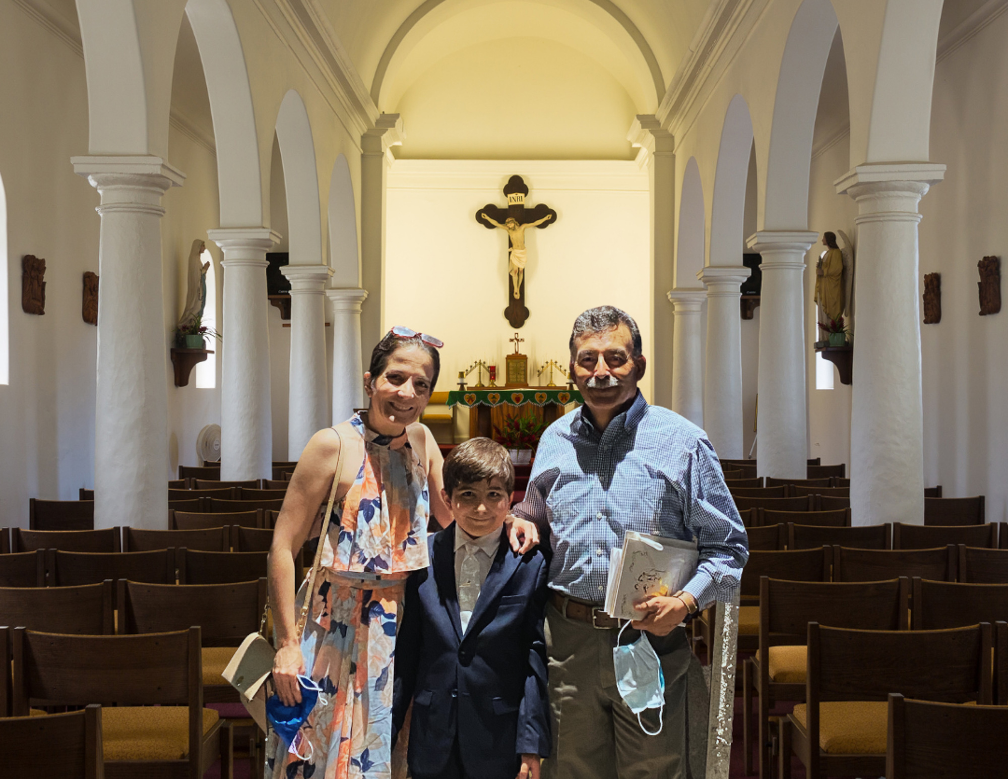 A mother and father stand in a church with a 10-year-old boy between them. They all smile at the camera. A crucifix can be seen in the background.