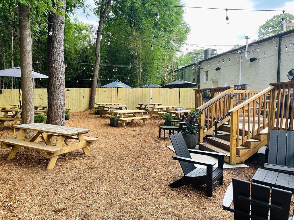 Empty picnic tables under tall shade trees and a round of Adirondack chairs populate the outdoor seating area in back of Red's Beer Garden in Benteen Park, Atlanta.