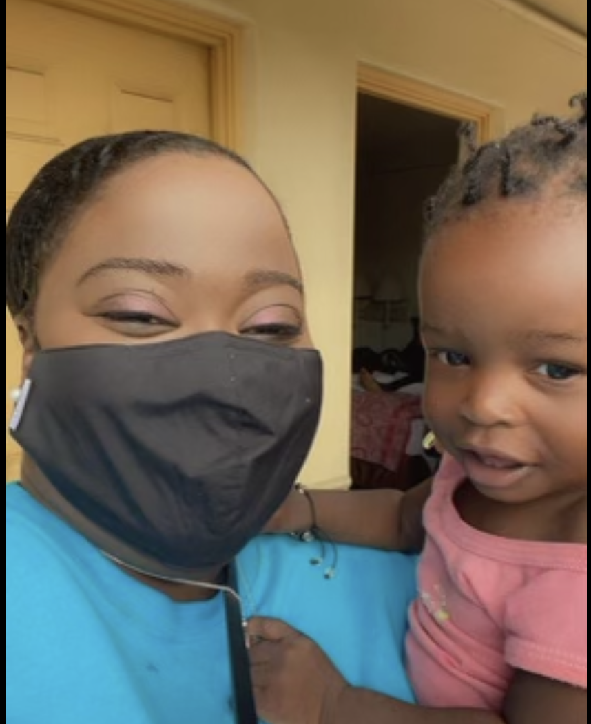 Patricia Nabal, pictured wearing a face mask, holds a child she met during a recent trip to the U.S. southern border to assess how the Haitian community in Chicago could help Haitian refugees.