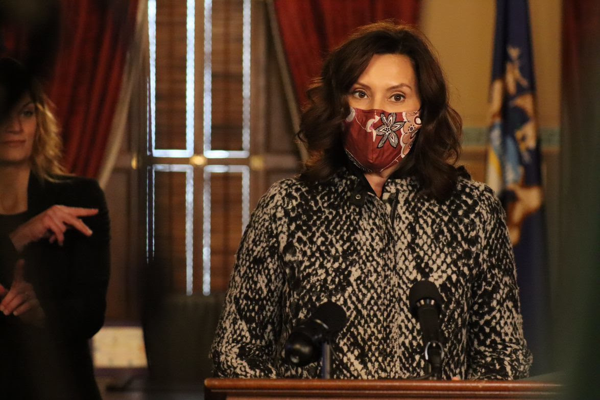 Michigan Governor Gretchen Whitmer speaks at a podium while wearing a protective mask.