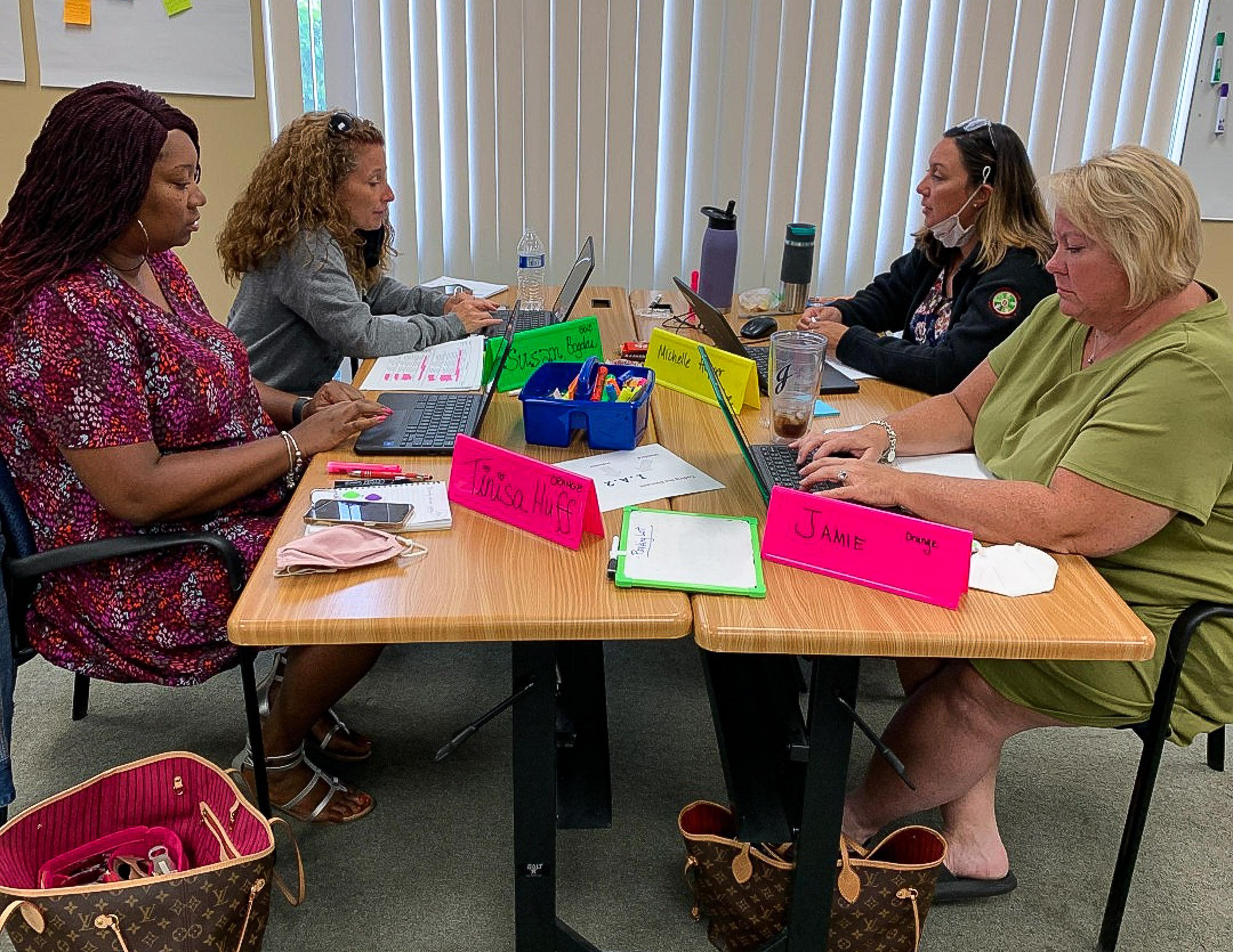 Four teachers from Forest Park sit at tables and work on laptops during professional development training.