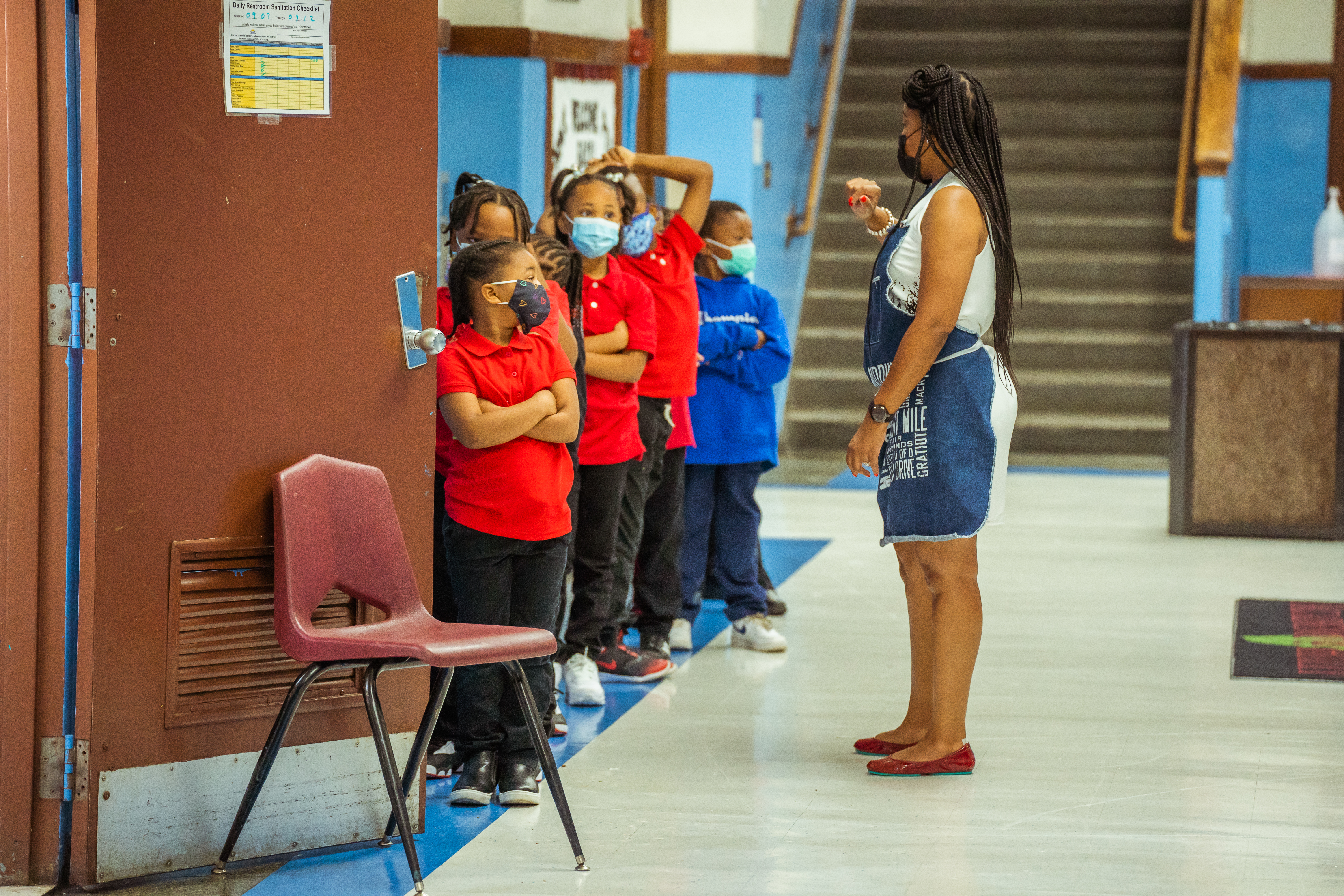 Students form in single-file line as a teacher provides instructions in a school hallway.