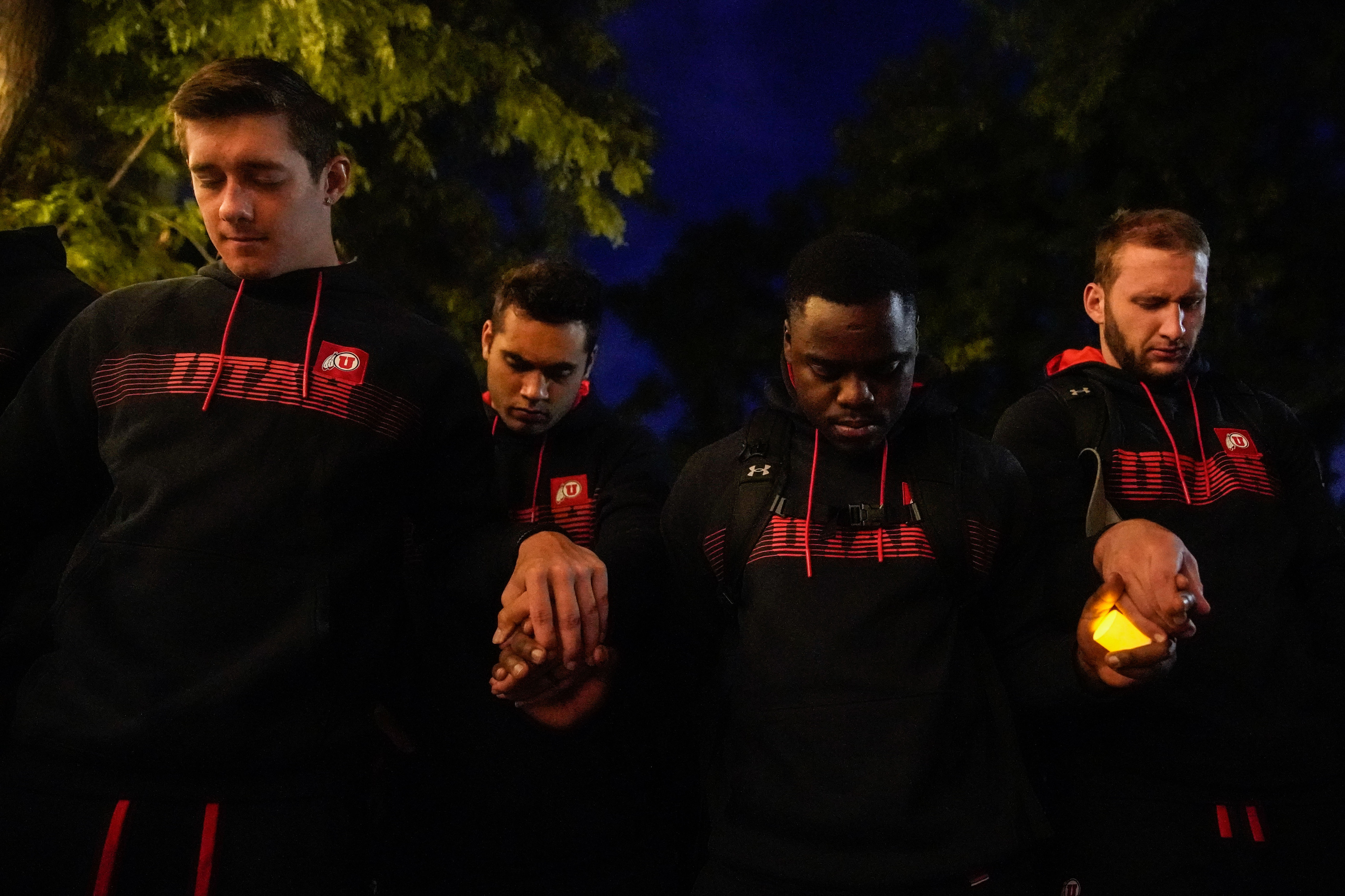 University of Utah football players, wearing black, holding hands pray during a candlelight vigil