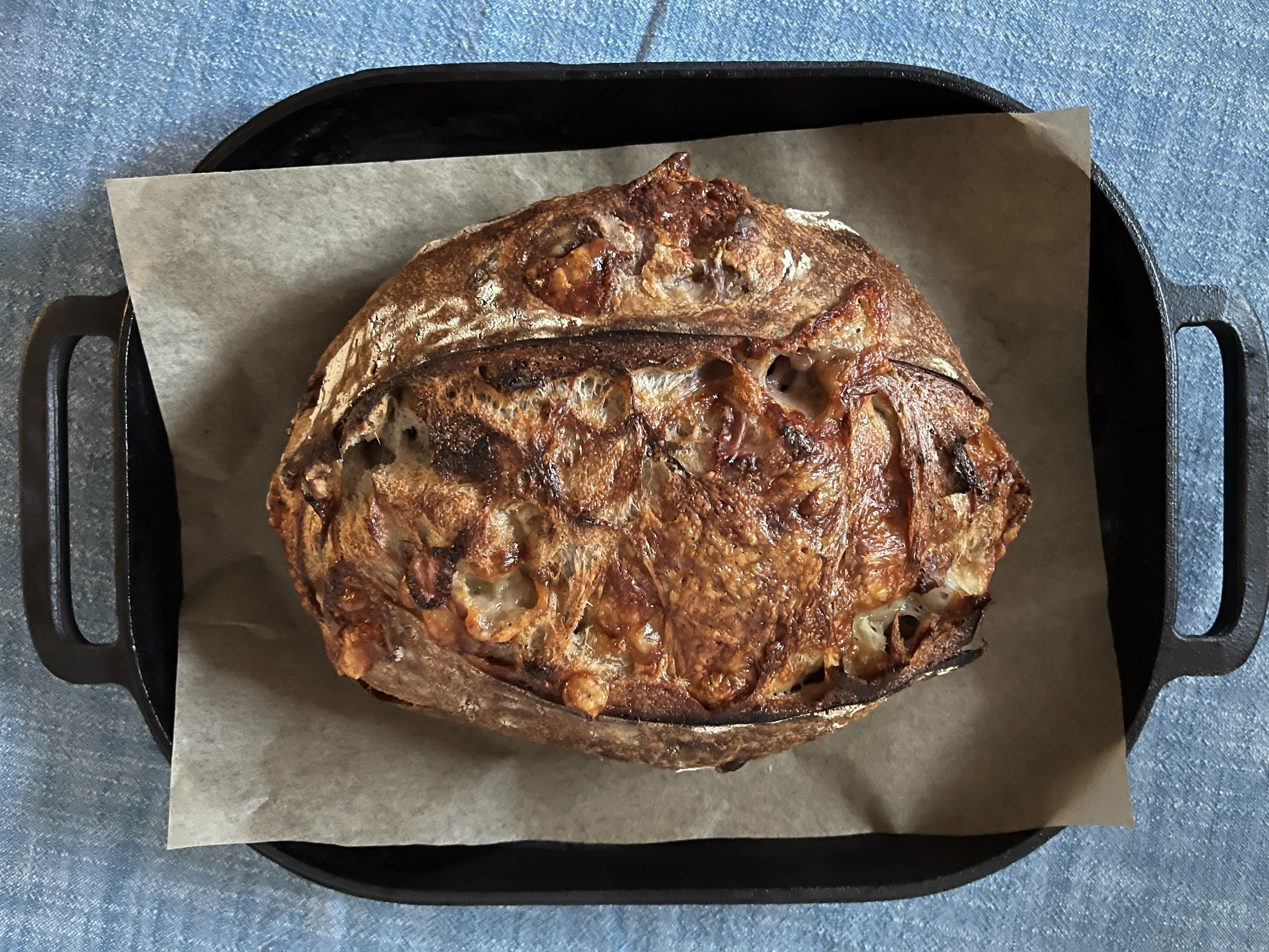 A loaf of strawberry and comte bread sots on a black baking pan on top of a blue tablecloth.