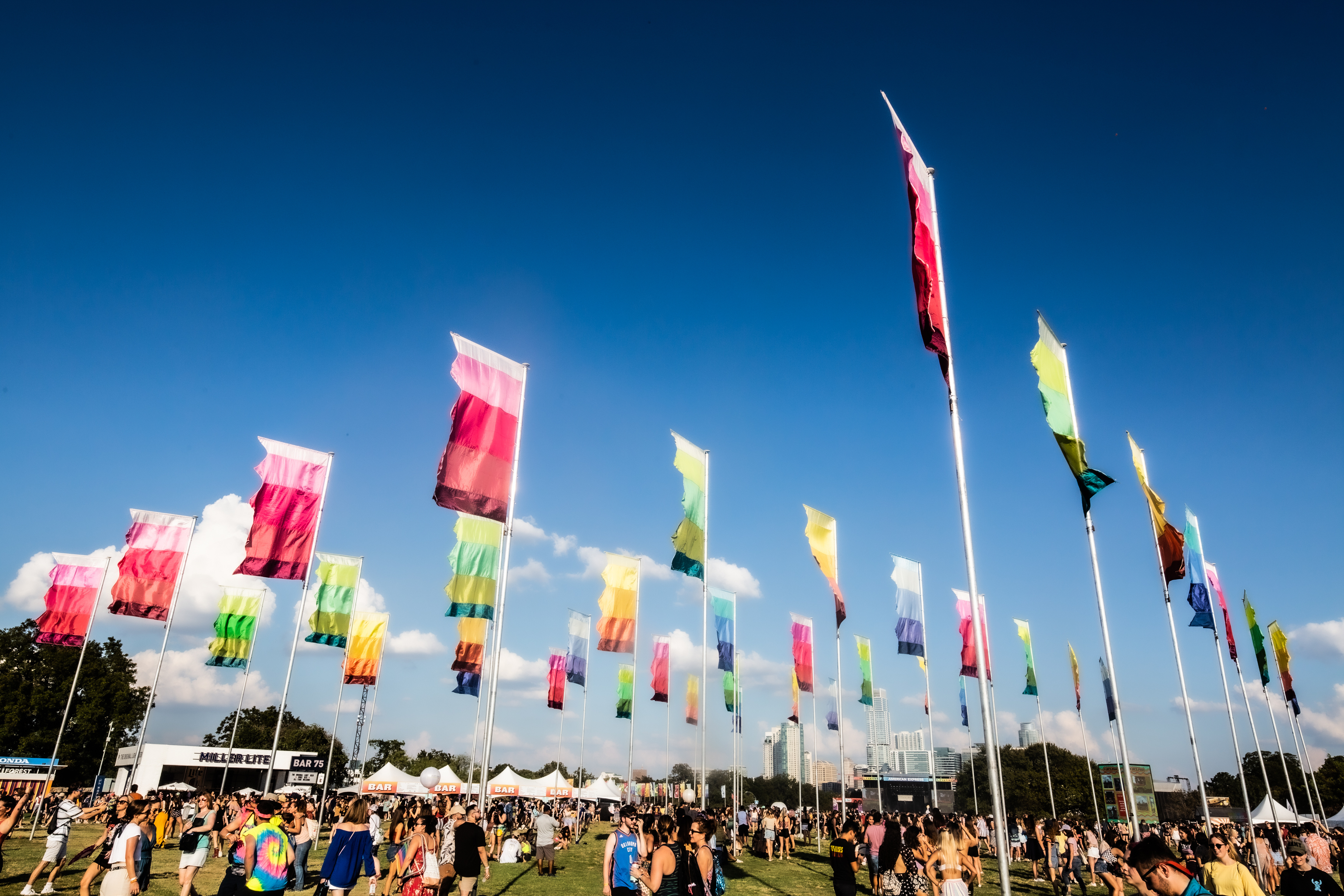 Tall colorful flags on masts blowing in the wind with a crowd of people on the ground