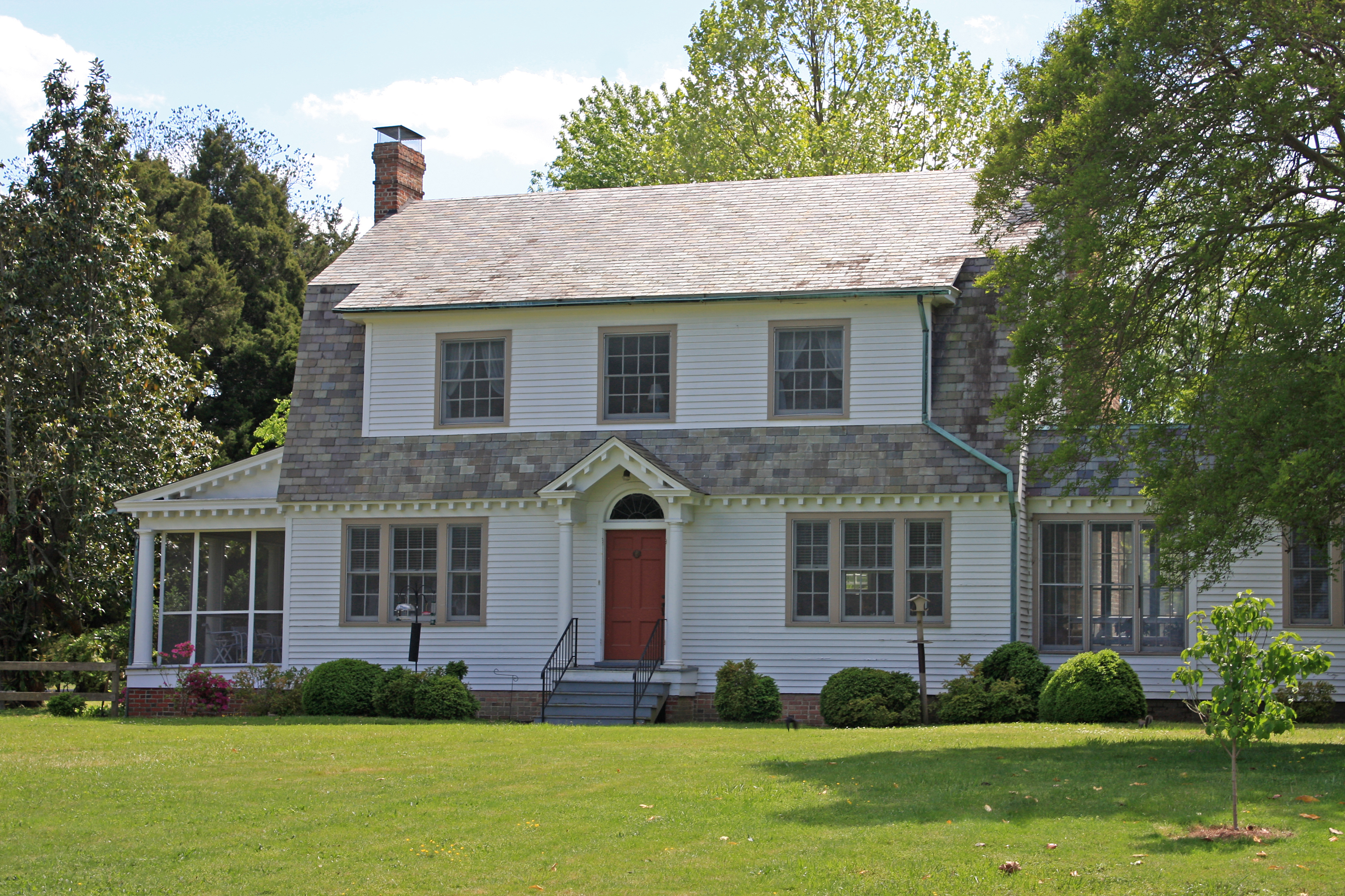 A white colonial style house with red front door, grey shingles, and large green front yard.