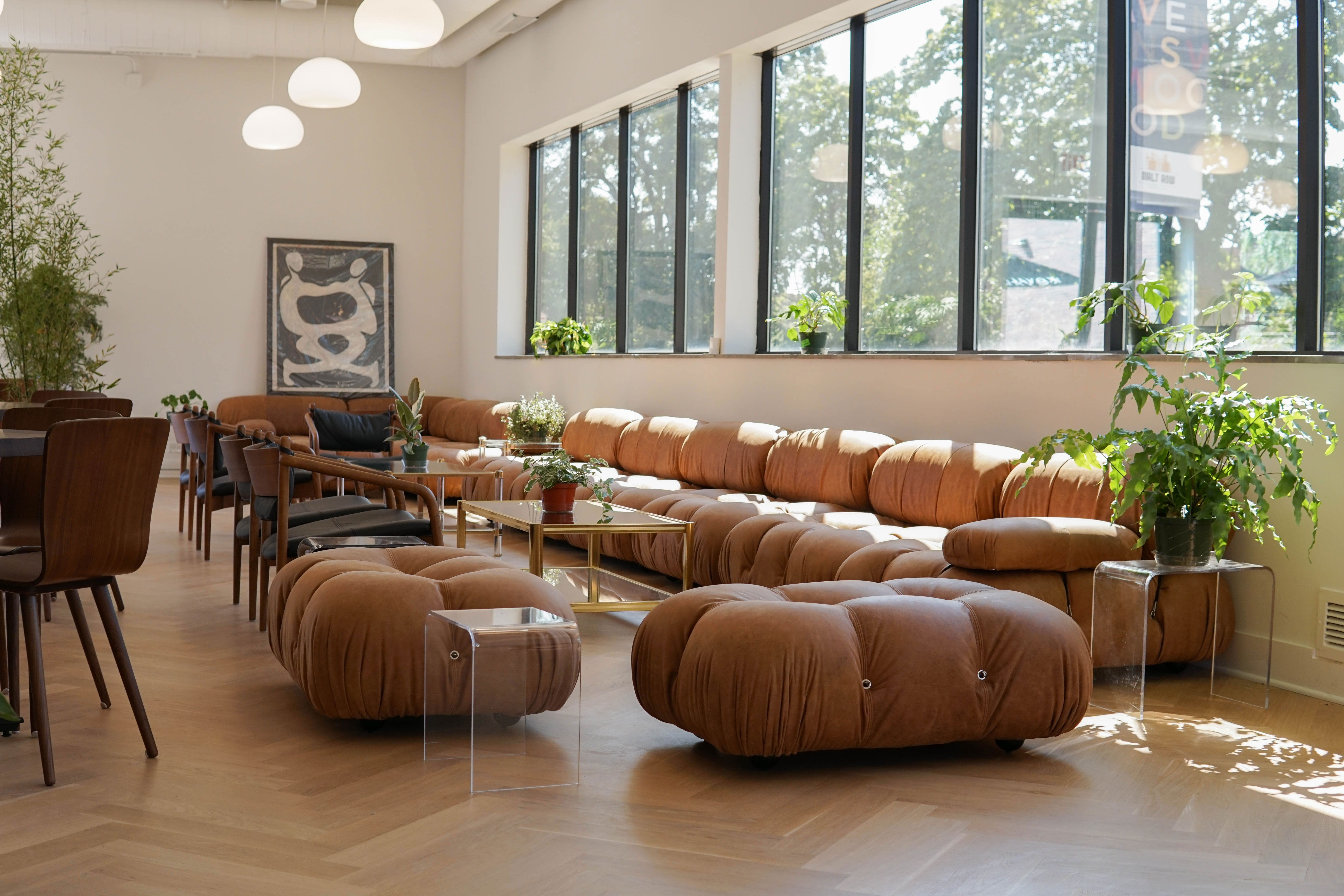A large tufted leather sofa sits inside a bright room with large windows