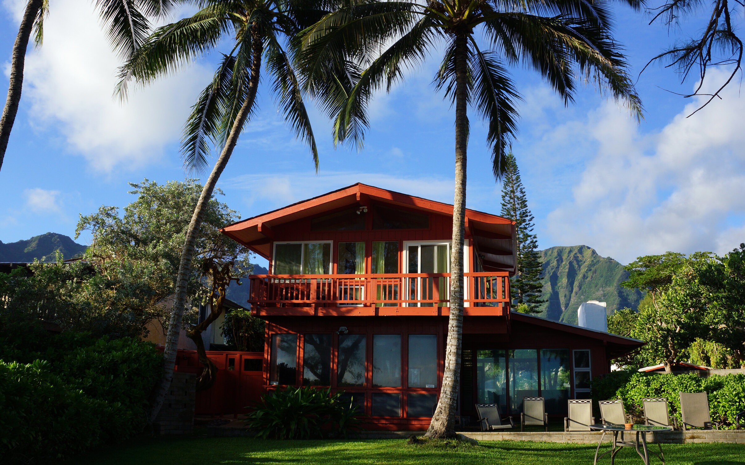 A red house in Hawaii with large palm trees and green yard.