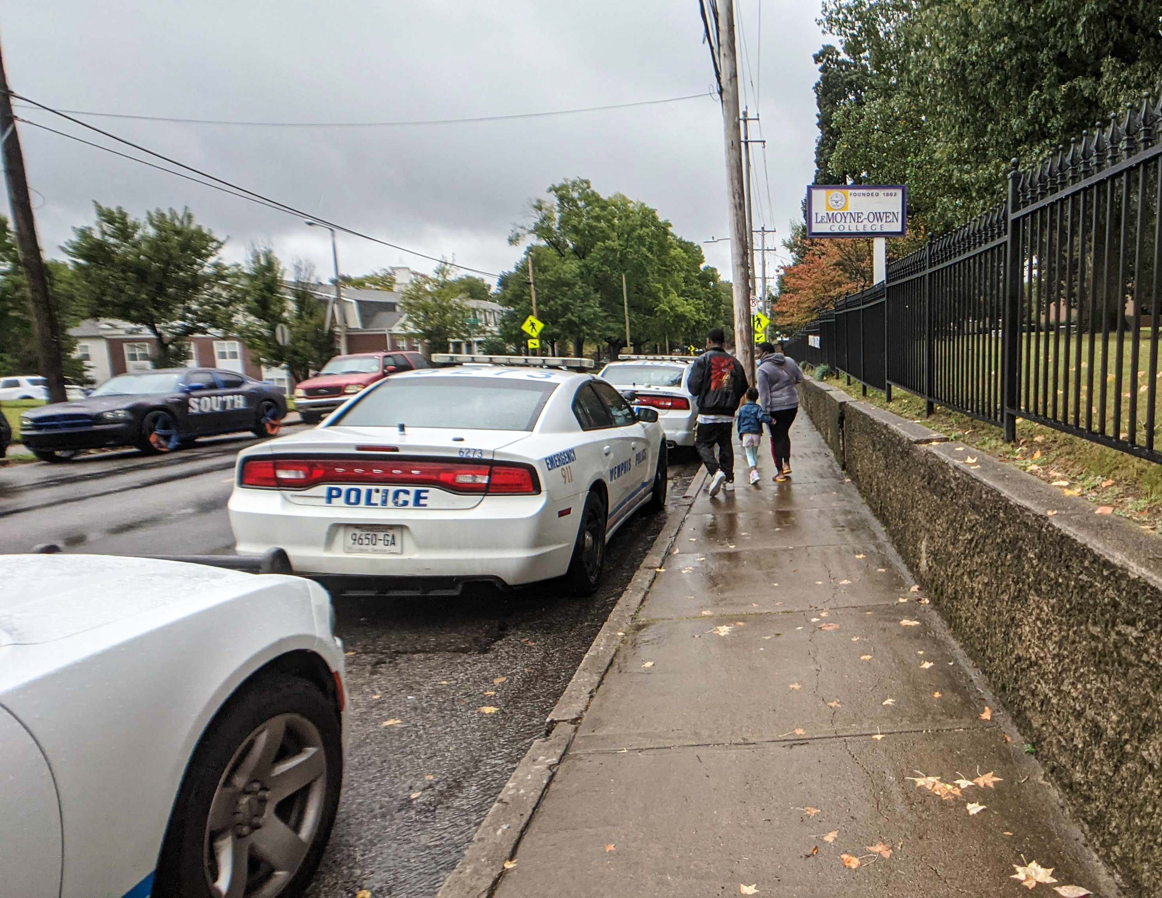 Parents walk past police vehicles following a shooting at Cummings Elementary School in Memphis.