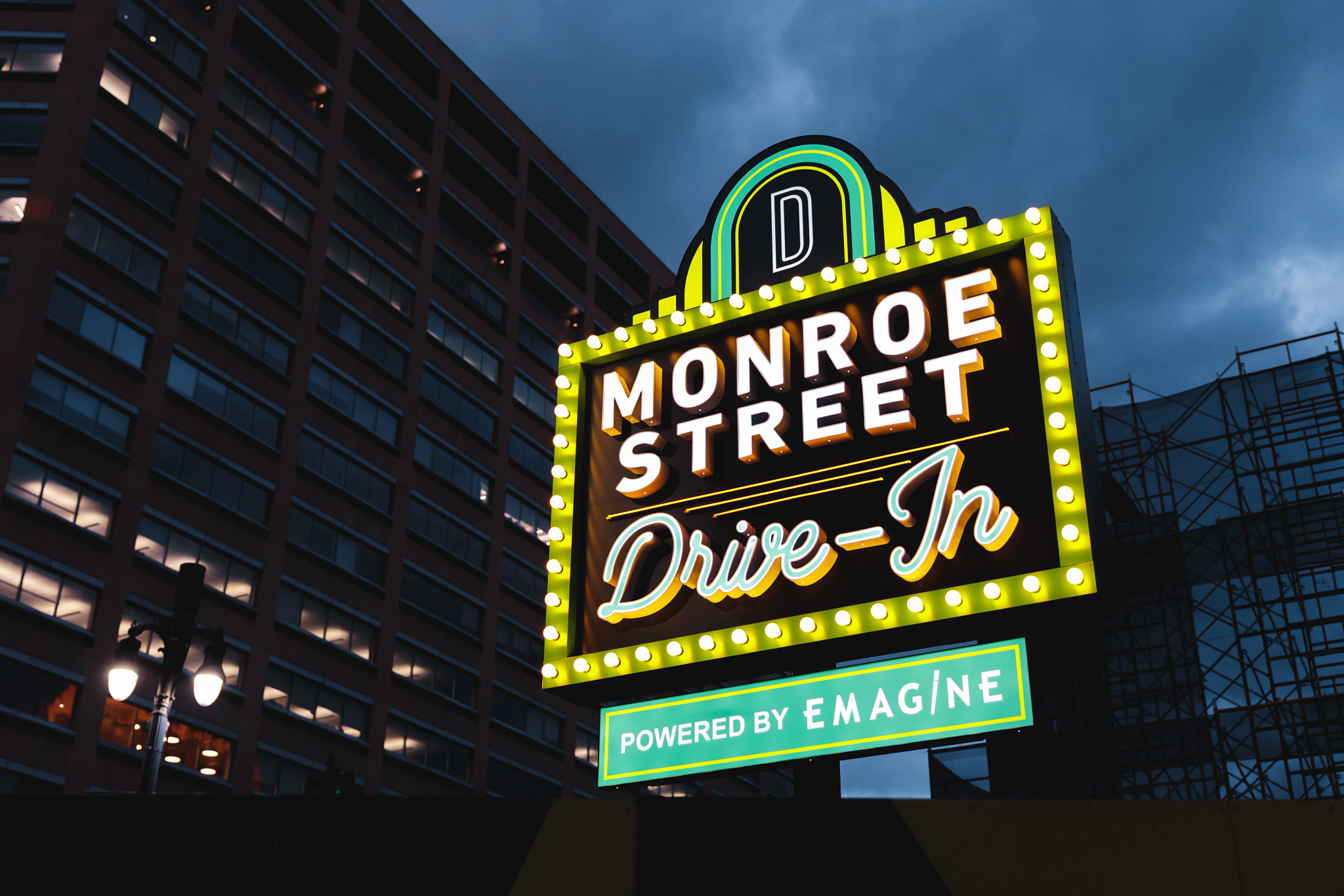 Green and yellow neon light up the sign for the Monroe Street Drive-In movie theater in downtown Detroit.