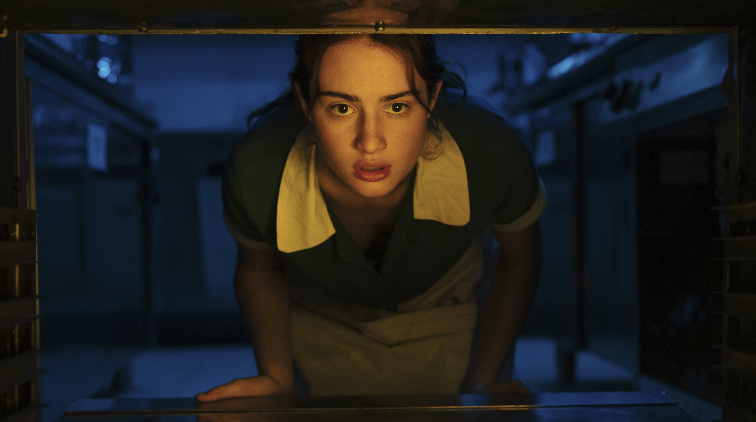 Grace Van Patten, dressed as a mid-century servant at a wedding venue, crawls through an oven and into a fantasy world in Mayday
