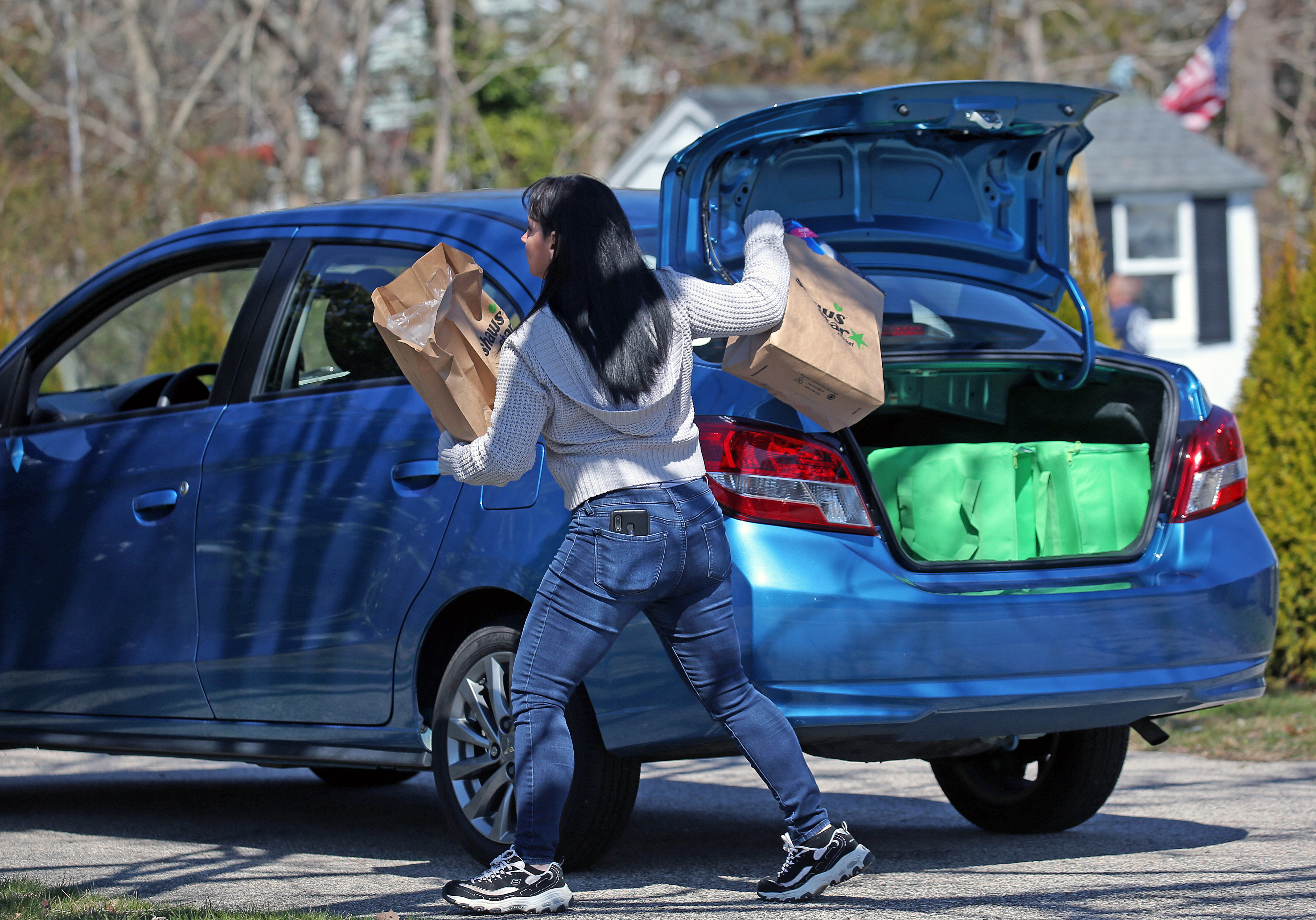 Instacart worker taking groceries out of her blue car's trunk