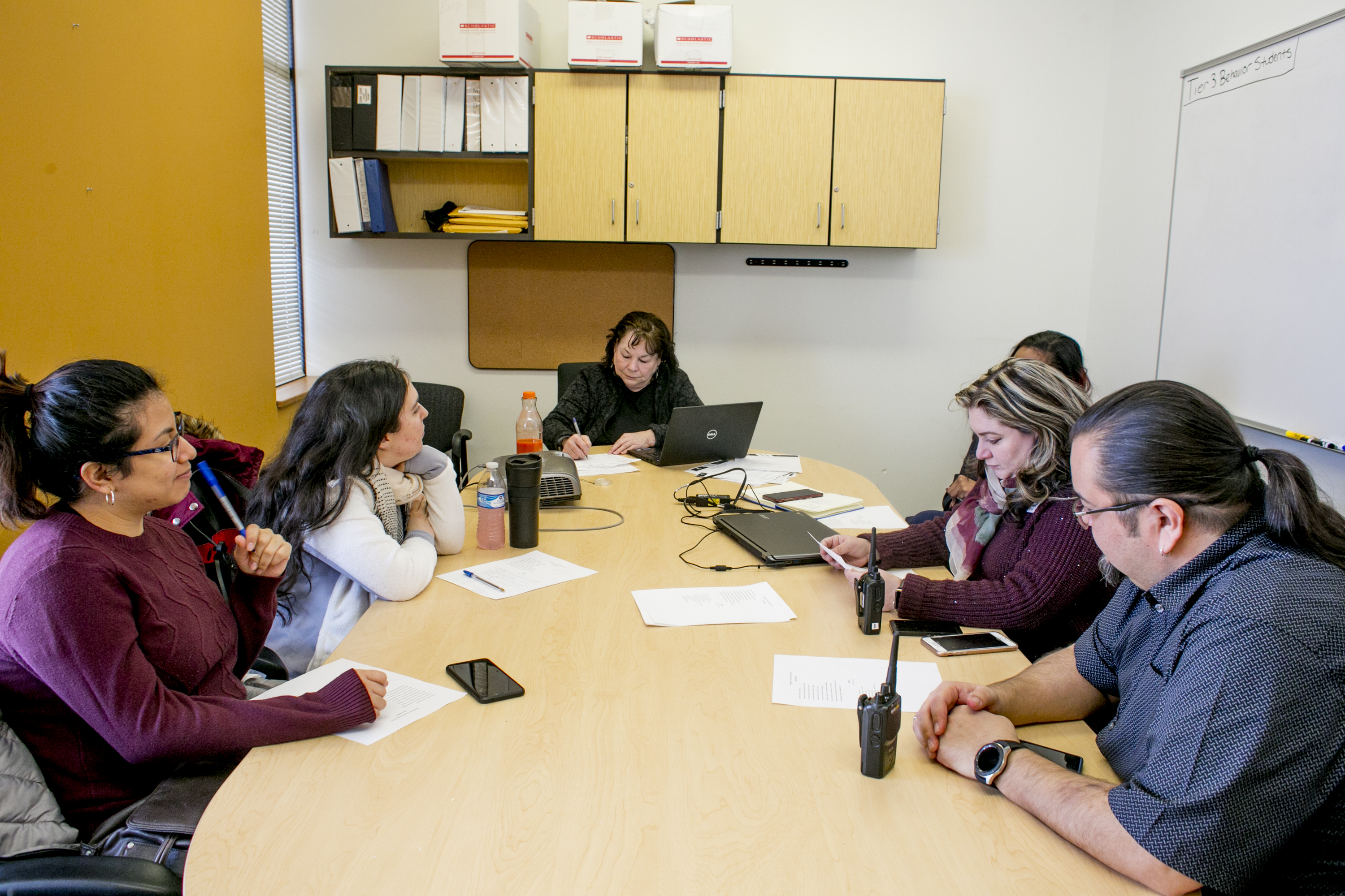 An attendance team meeting at Earhart Elementary-Middle School in southwest Detroit includes staff from the school and a community organization.