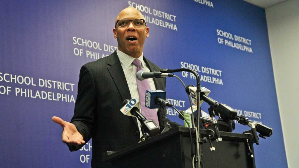 Philadelphia Superintendent William Hite stands at a podium surrounded by microphones.