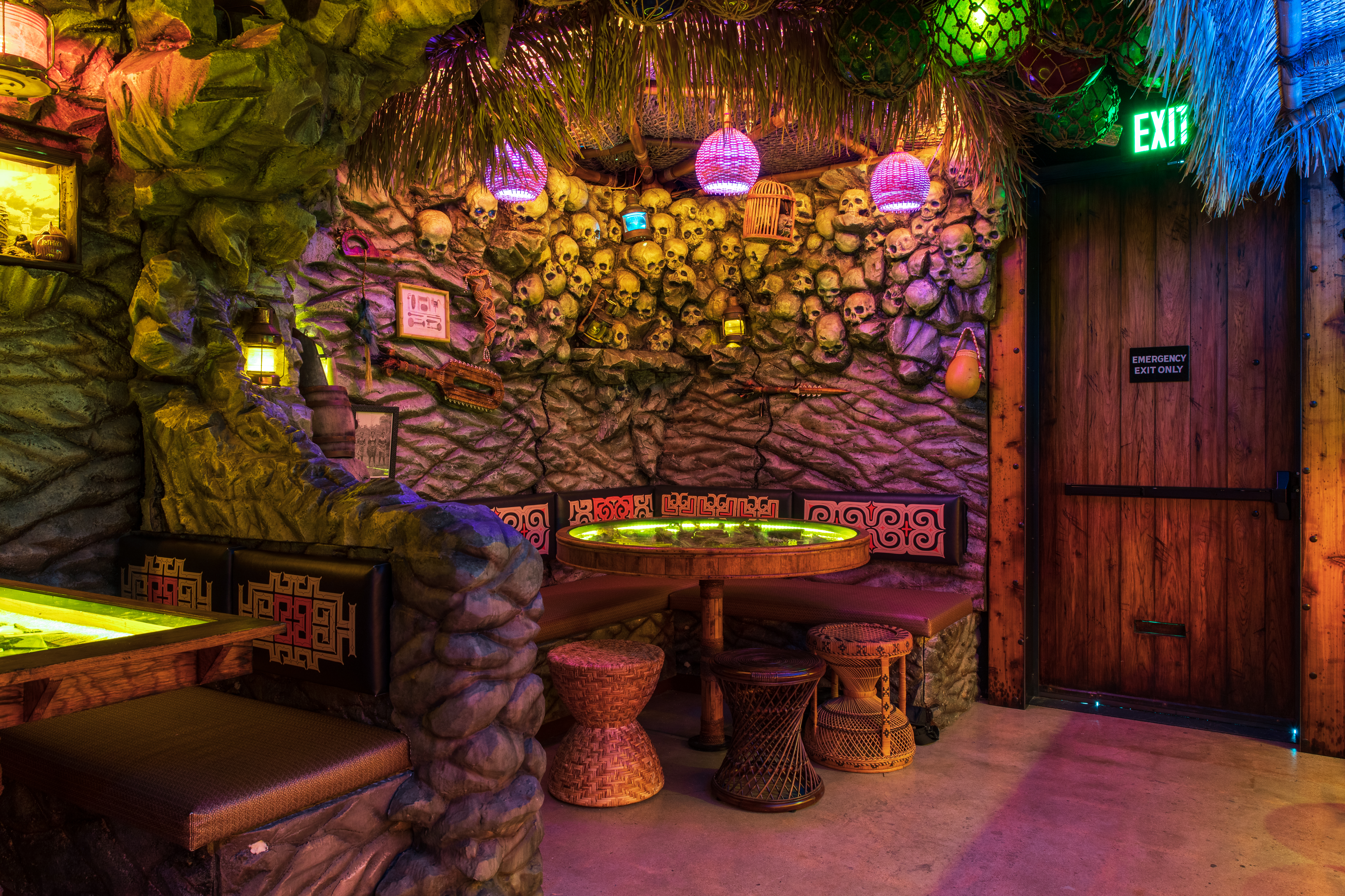 Under colorful lamps, fronds, and netting, a corner booth is nestled into a rock wall inlaid with skulls.