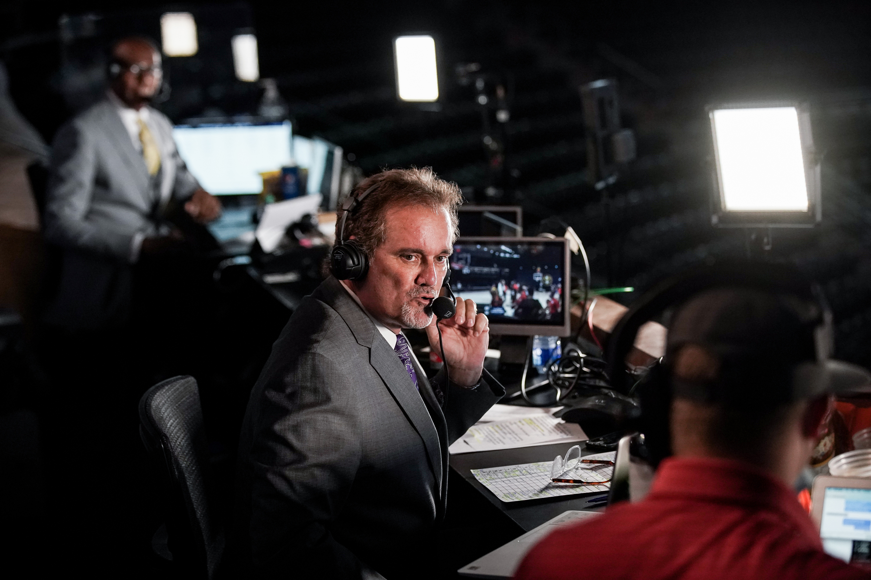 Craig Bolerjack, wearing a suit and tie, calls the play-by-play.