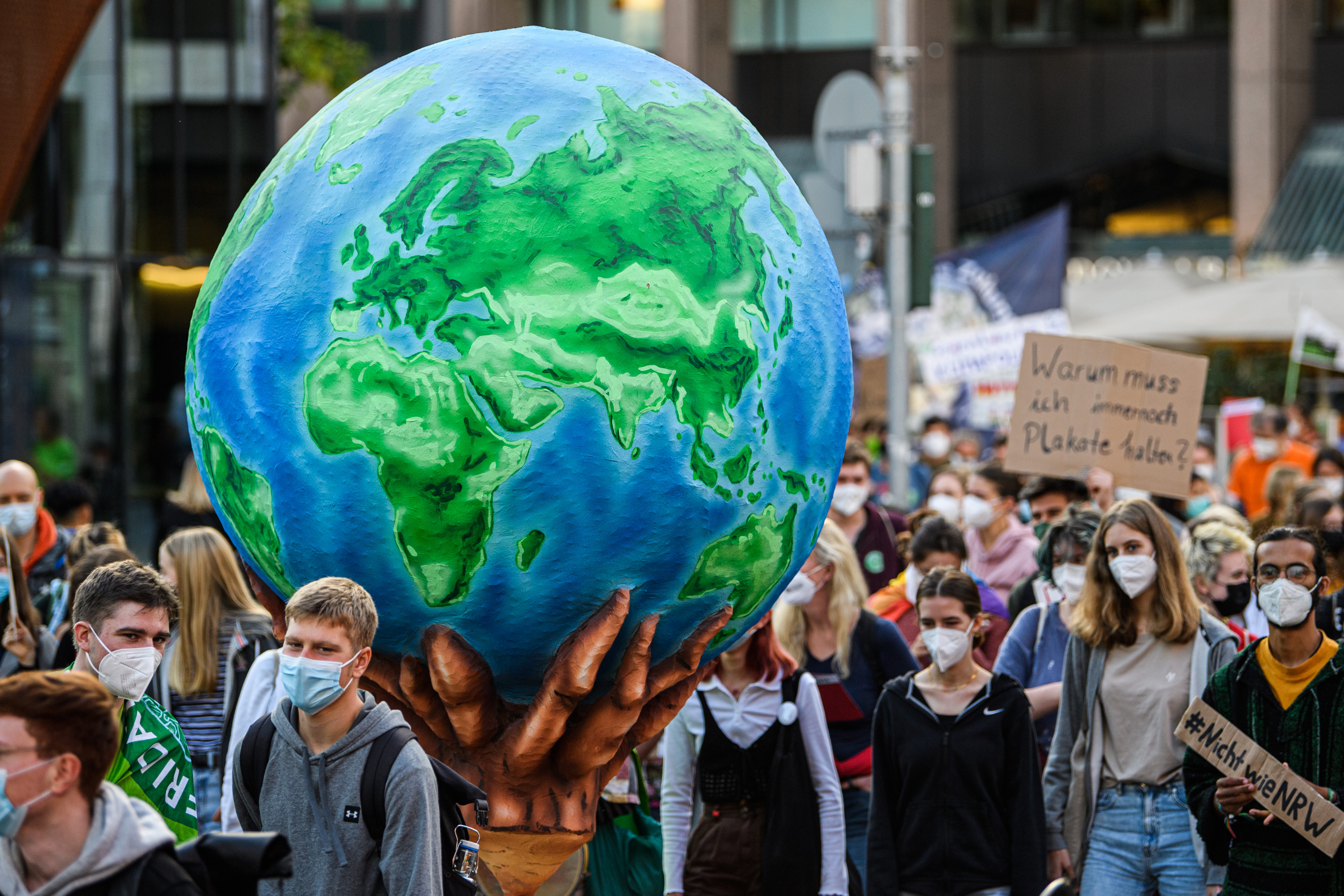 Protesters carry down an urban street a huge model of the earth with flames at its base.