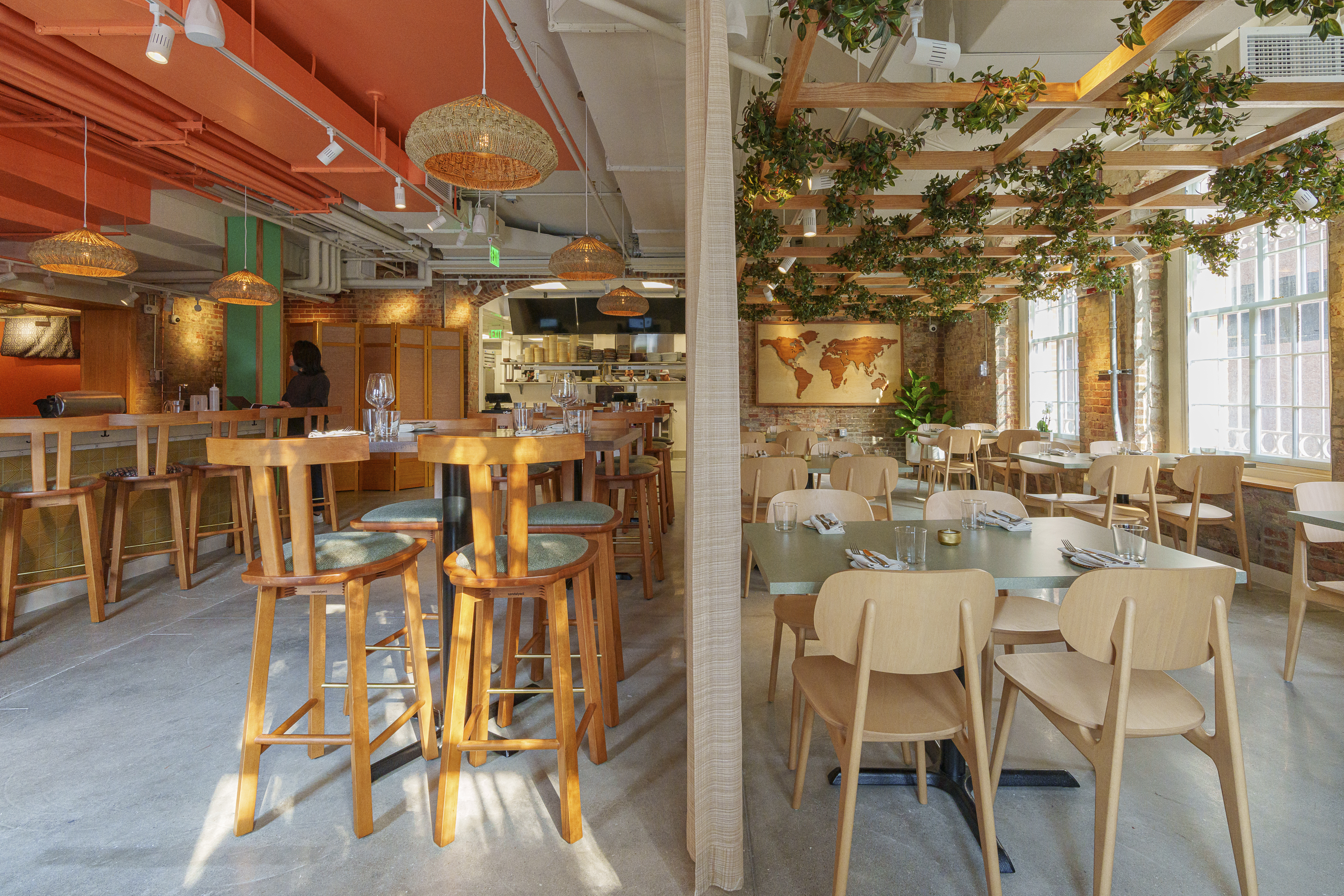 Sections of the dining room at Immigrant Food + are split between an orange ceiling and wooden frames with hanging plants.