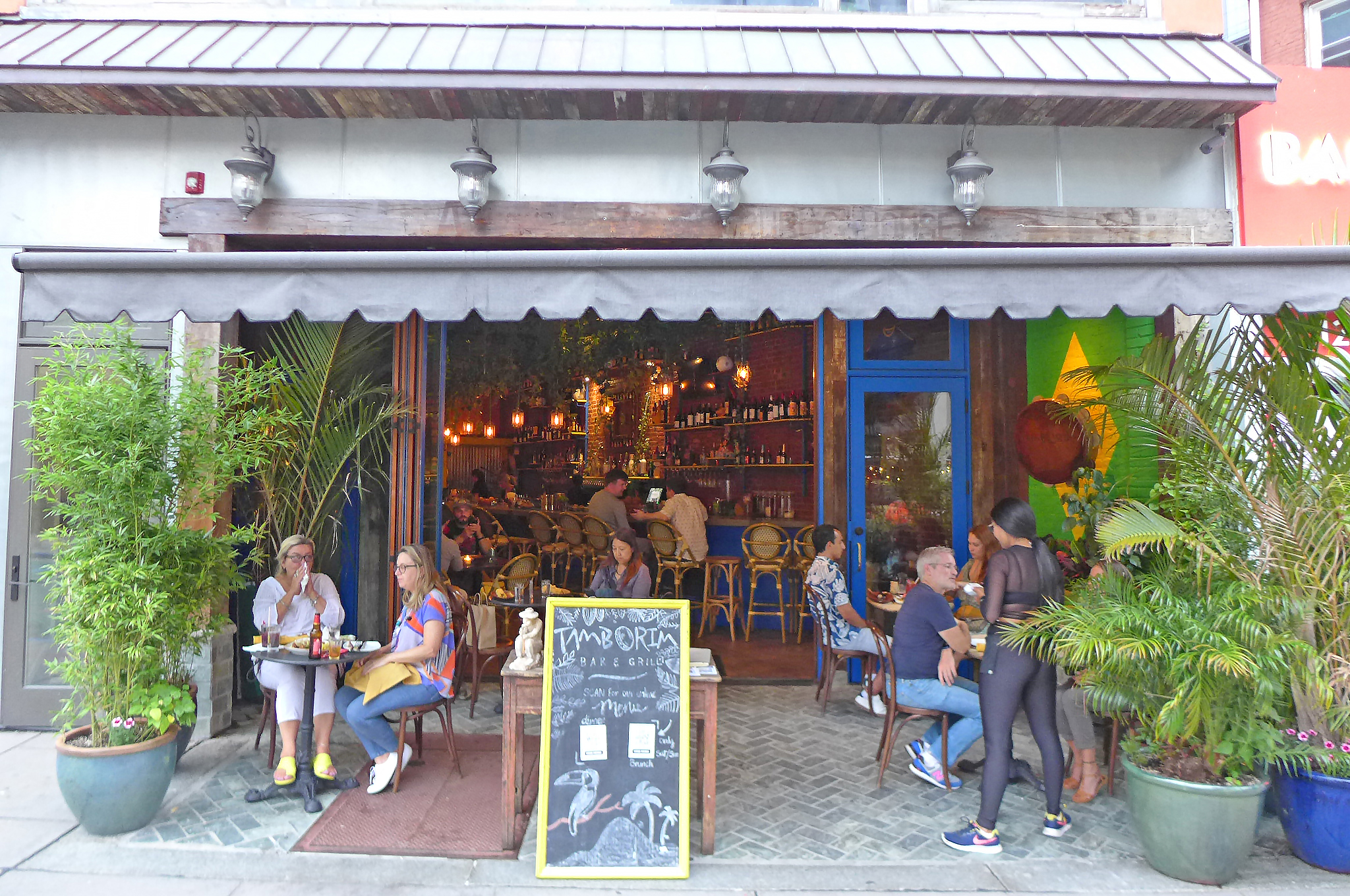 A open storefront with tables on the sidewalk amid potted foliage, looking into a bar.