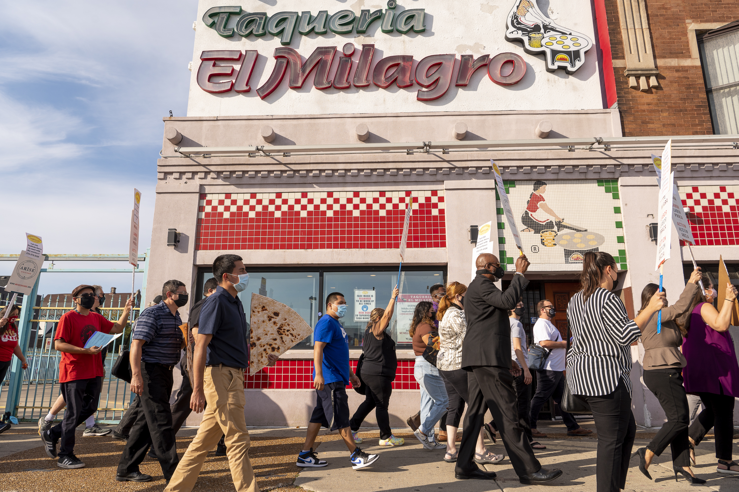A group of workers, supporters, and elected officials march towards El Milagro's headquarters for a press conference.