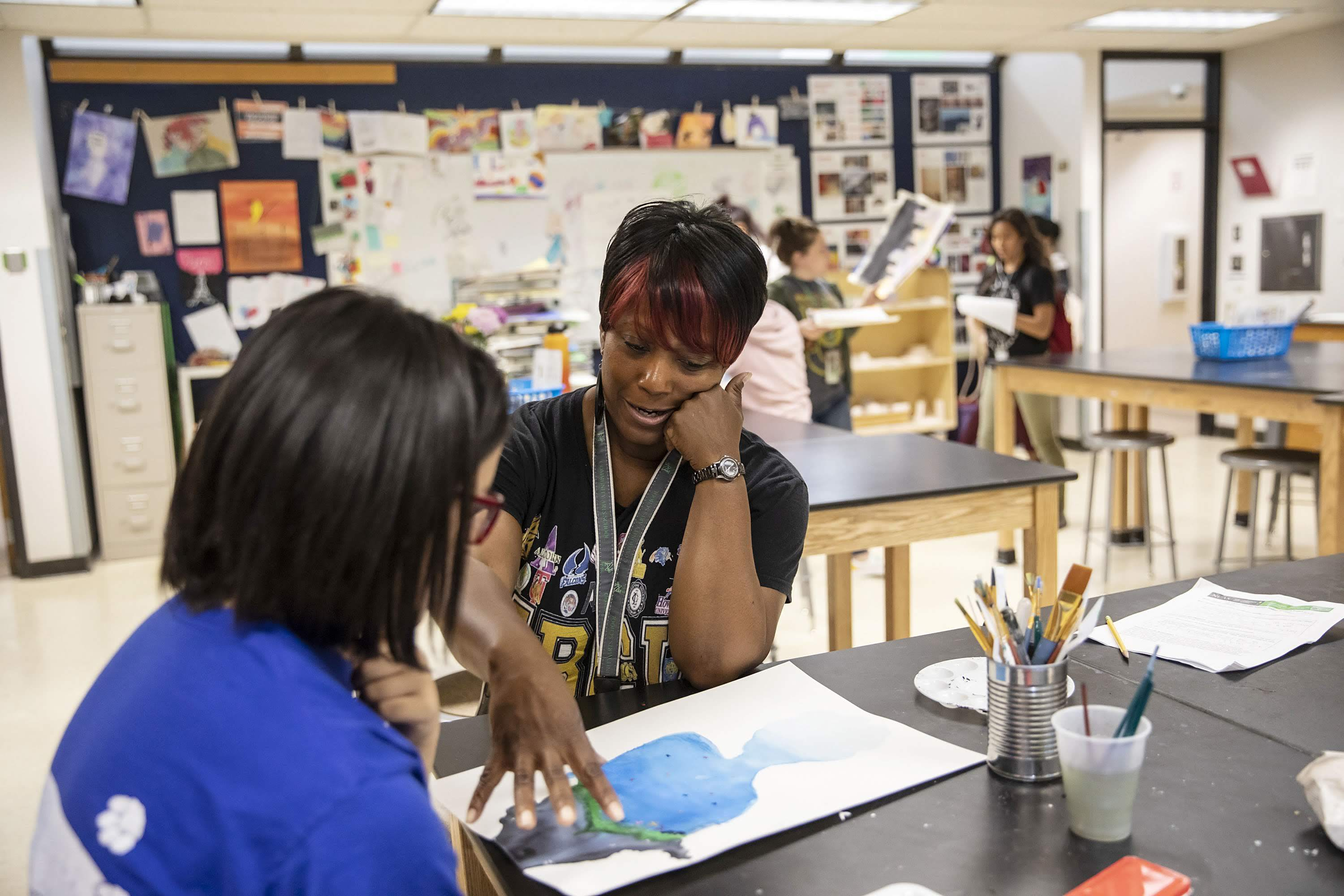 A teacher with a lanyard around her neck works with a student in an art class as they look at a watercolor on a table.