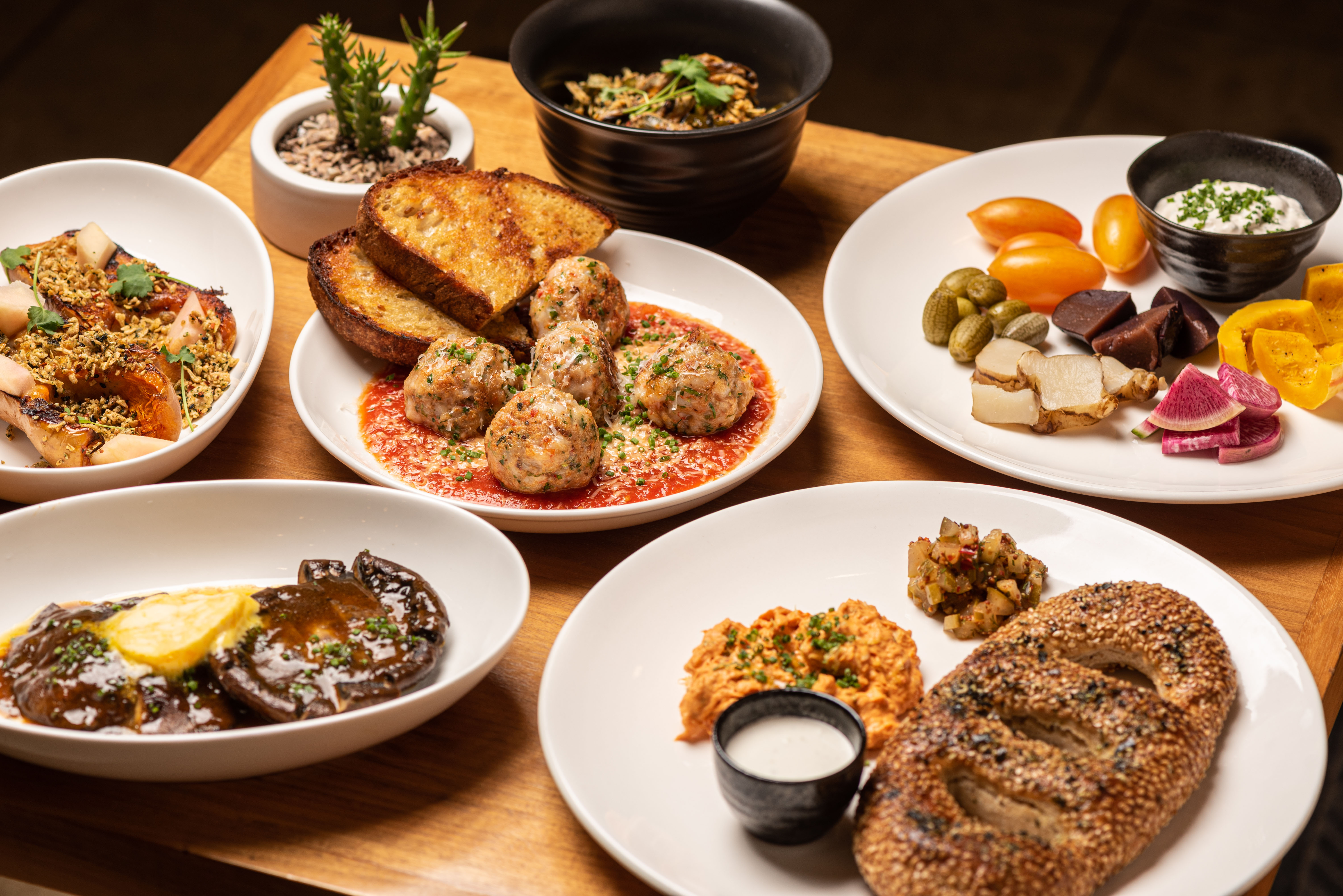 A side-tilted view of a table filled with dinner food including vegetables and meatballs.