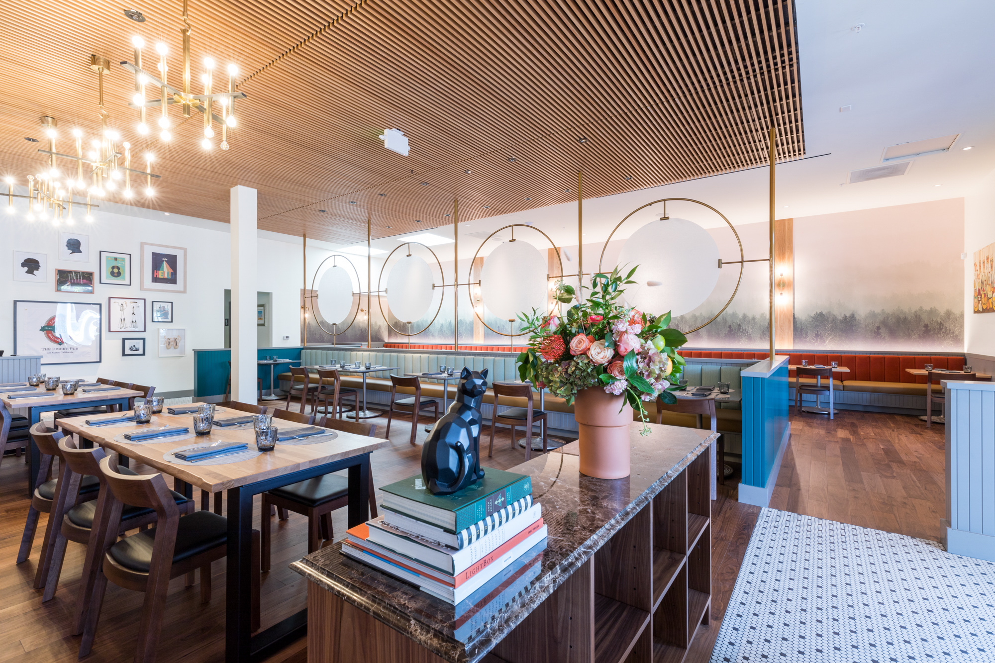 The interior of Shepherd & Sims with a mosaic tile floor, wooden tables, and white walls. Pops of color include a turquoise half-wall and a vase of flowers on the hostess stand.