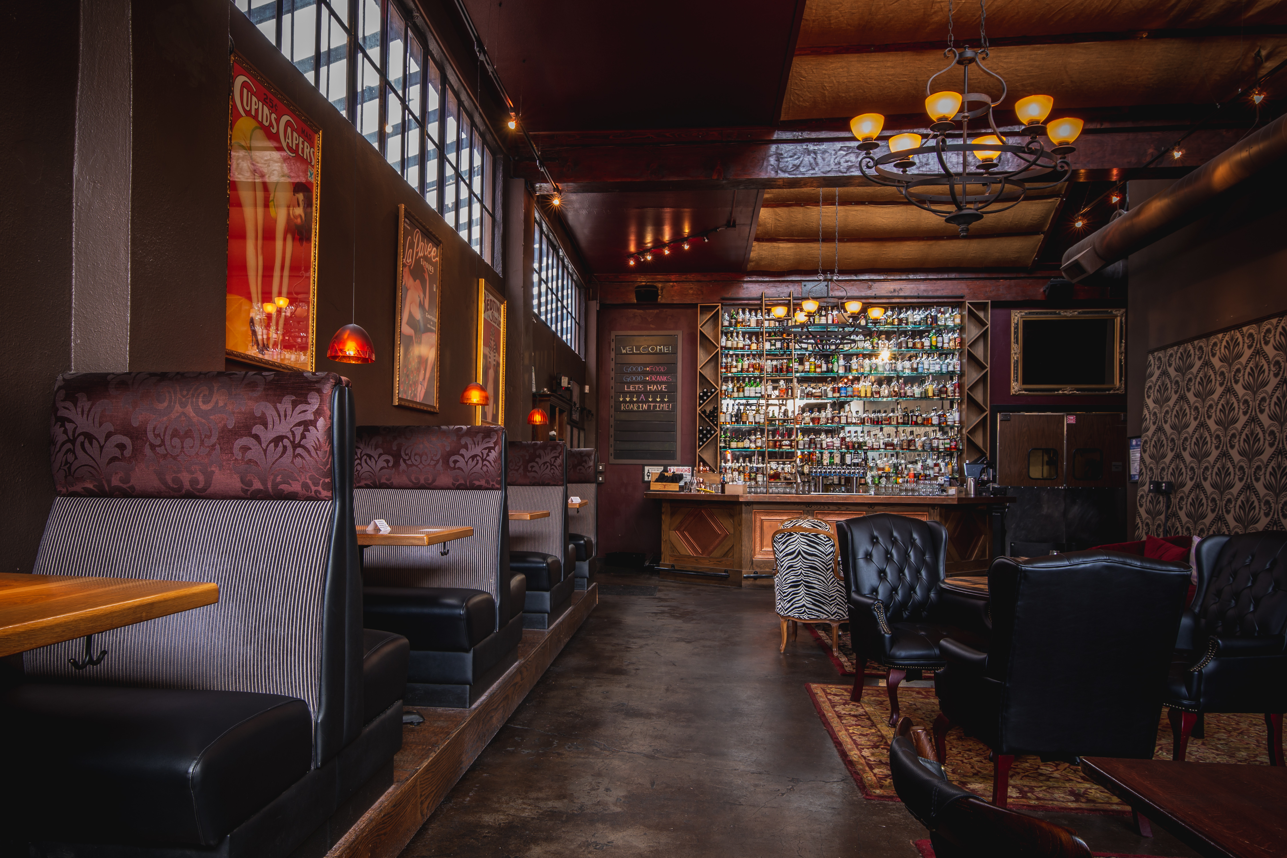 An empty dining room with a tall back bar, black tufted leather seats, and vintage booths.
