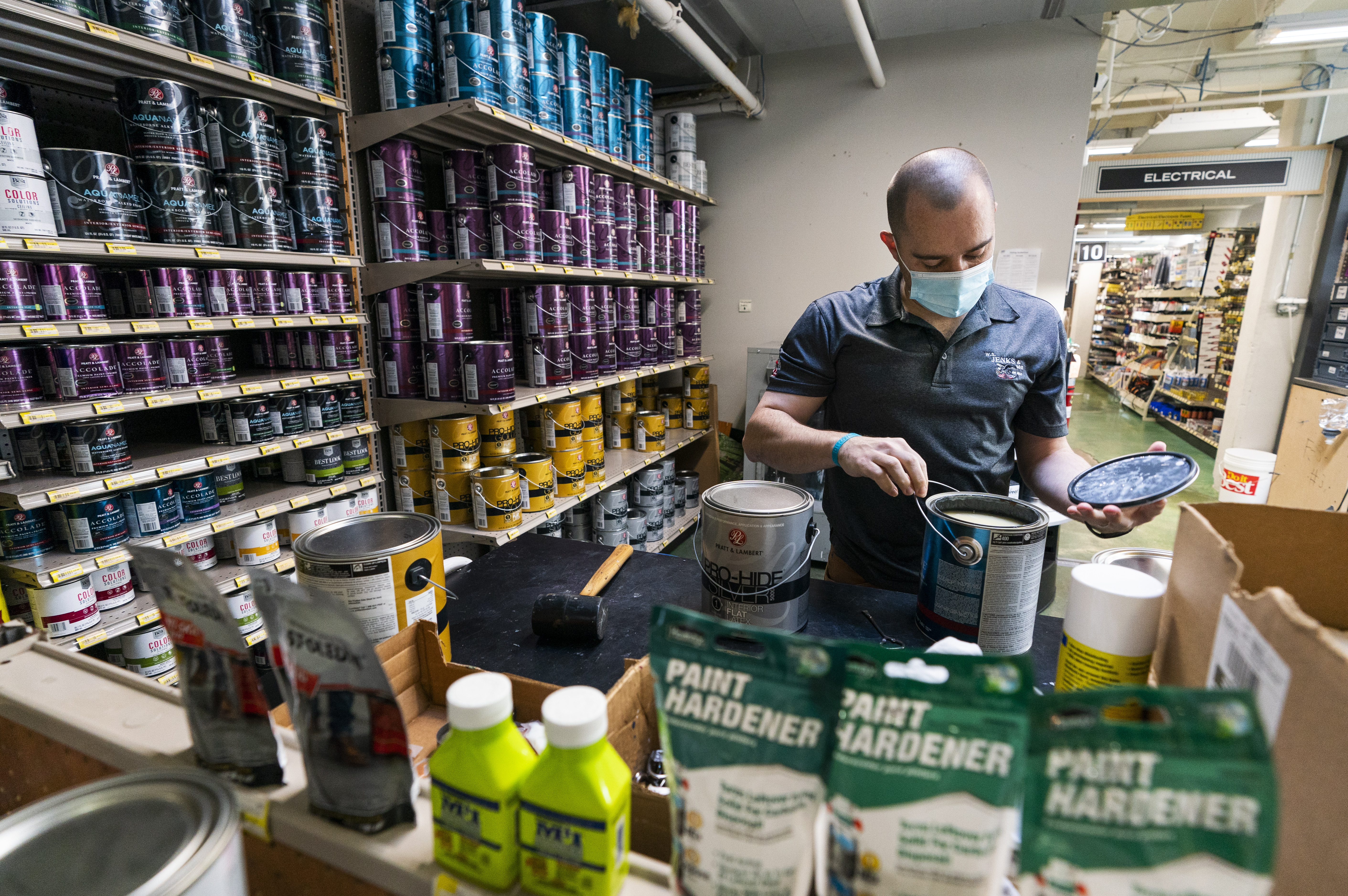 Billy Wommack, purchasing director at the W.S. Jenks & Sons hardware, opens a gallon of paint at the mixing station of the hardware store's paint department. Paint is among the goods costing more because of a shortage of chemicals used in manufacturing.