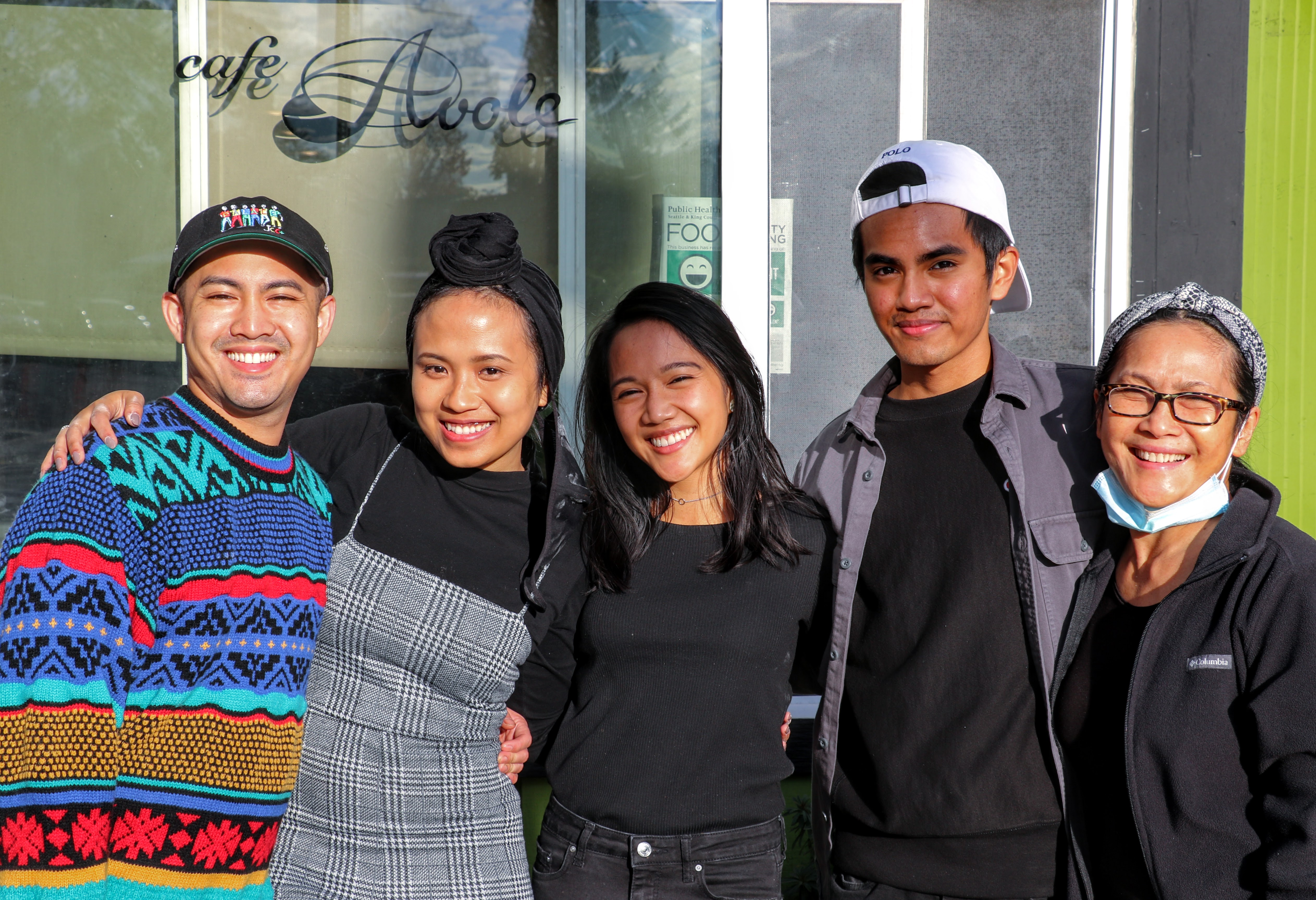Five family members stand together smiling in front of a cafe.