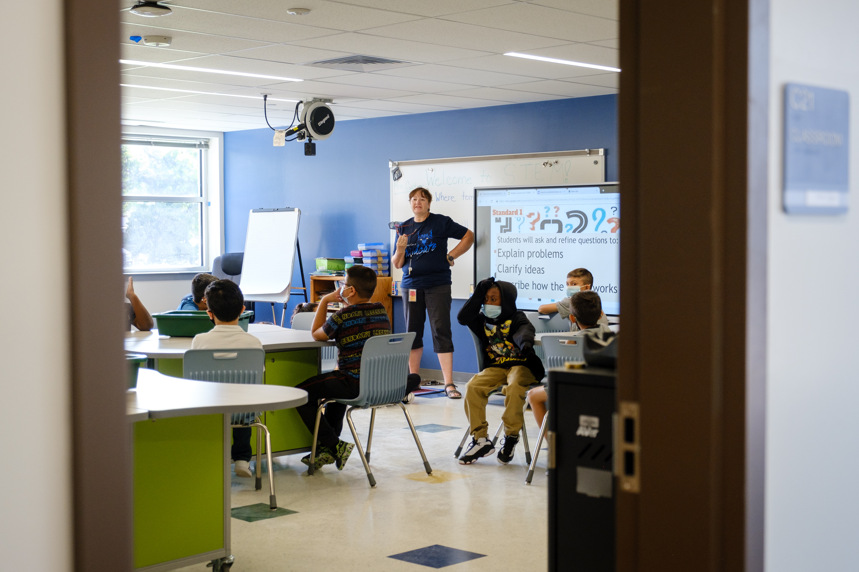 A teacher speaks to her students during a STEM class. The classroom is partially obscured by the doorframe.