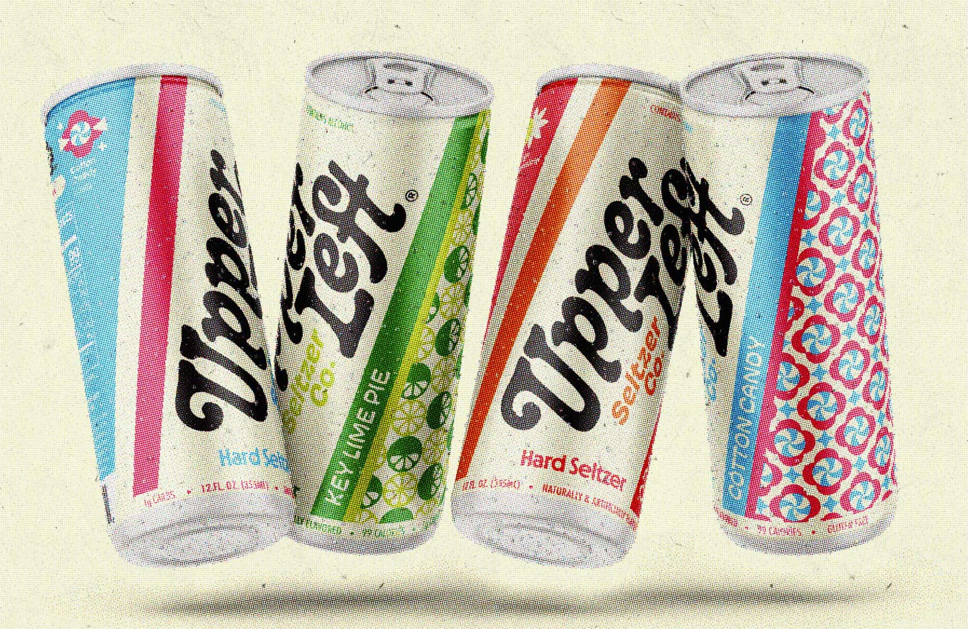 Four cans, designed with '70s-style font and colorful patterns, hover in front of an off-white backdrop.