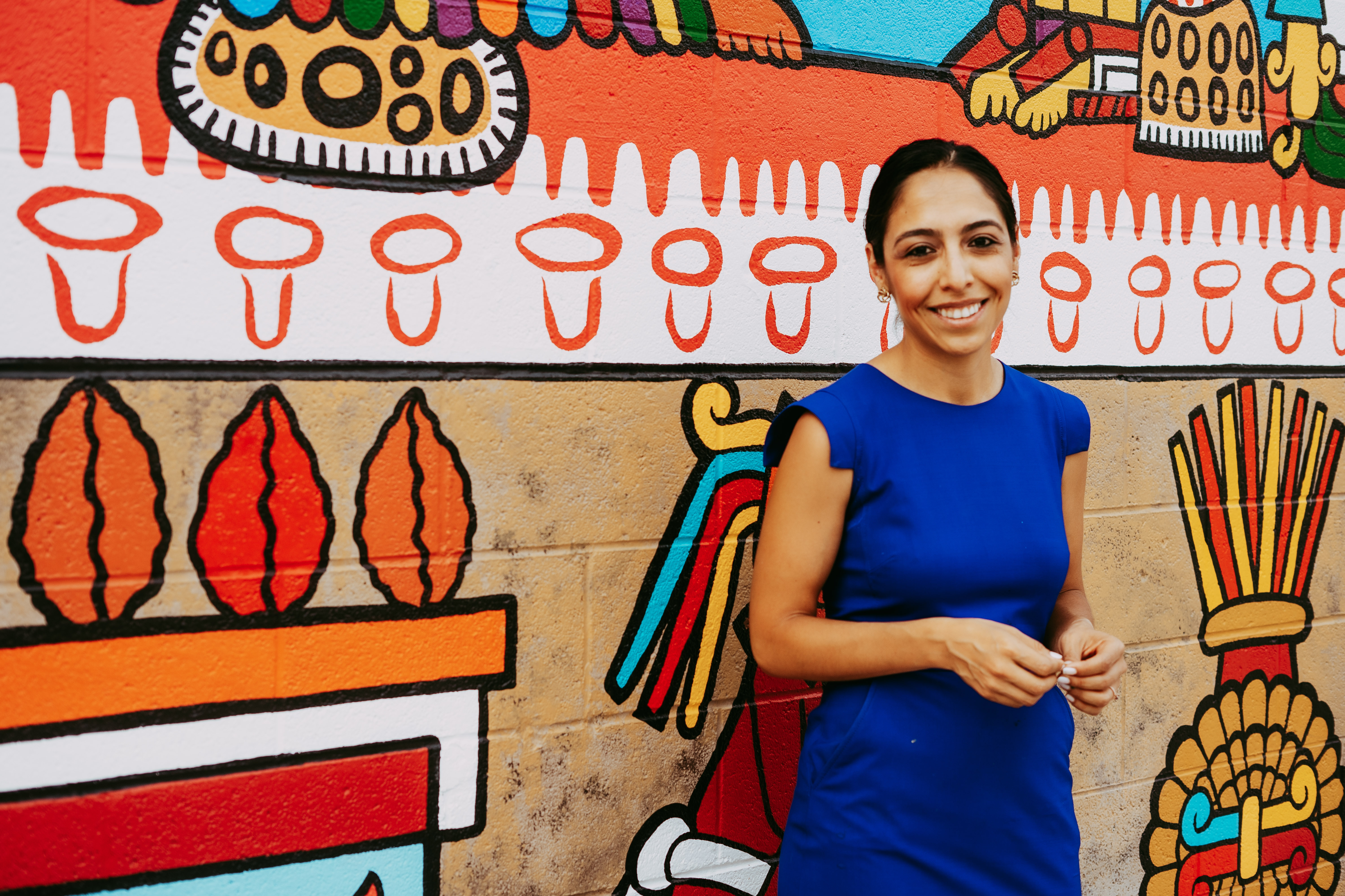 A woman wearing a blue dress poses in front of a brightly colored mural.