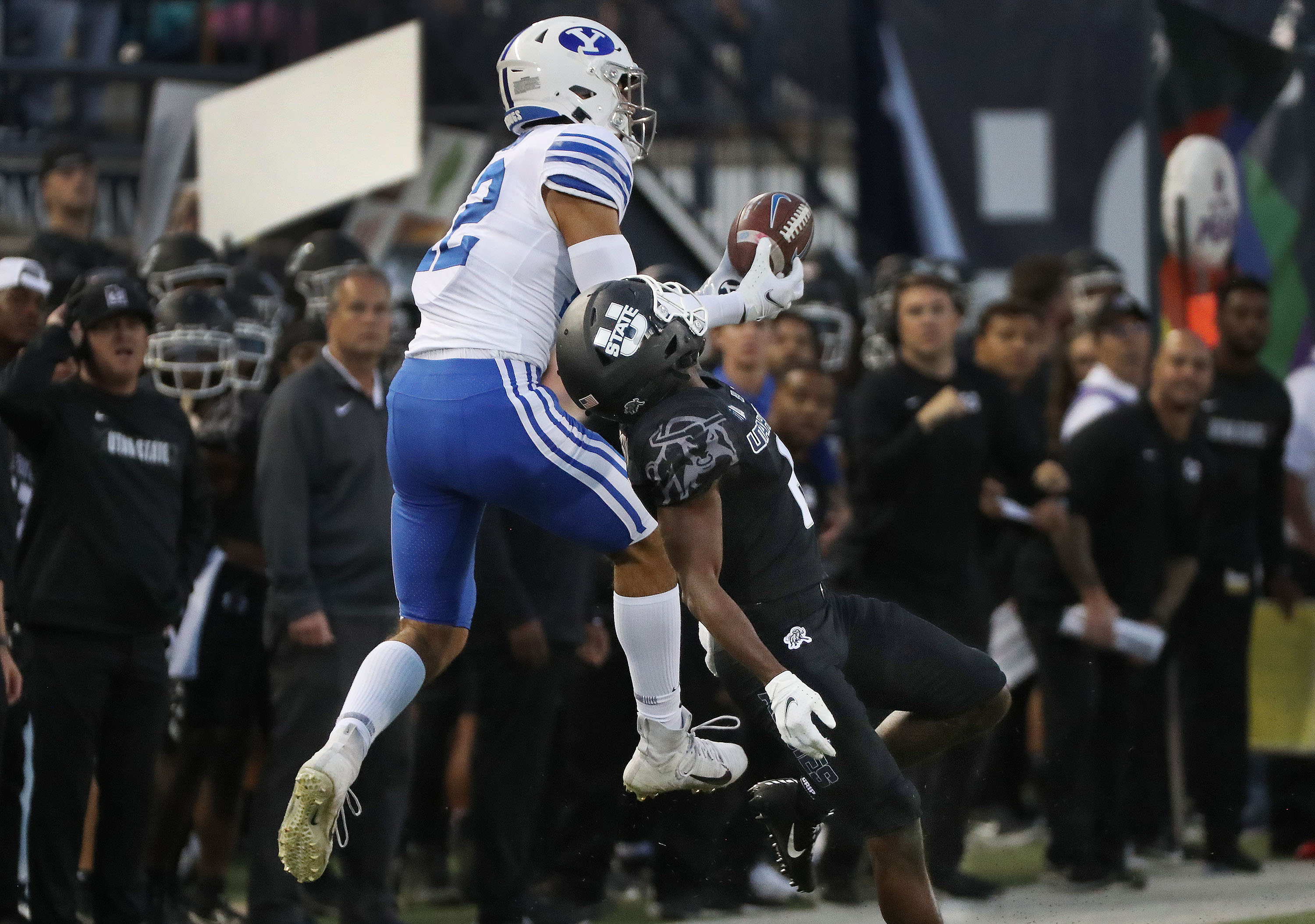 Brigham Young Cougars wide receiver Puka Nacua (12) grabs a pass over Utah State Aggies cornerback Cam Lampkin (6) in Logan on Friday, Oct. 1, 2021.