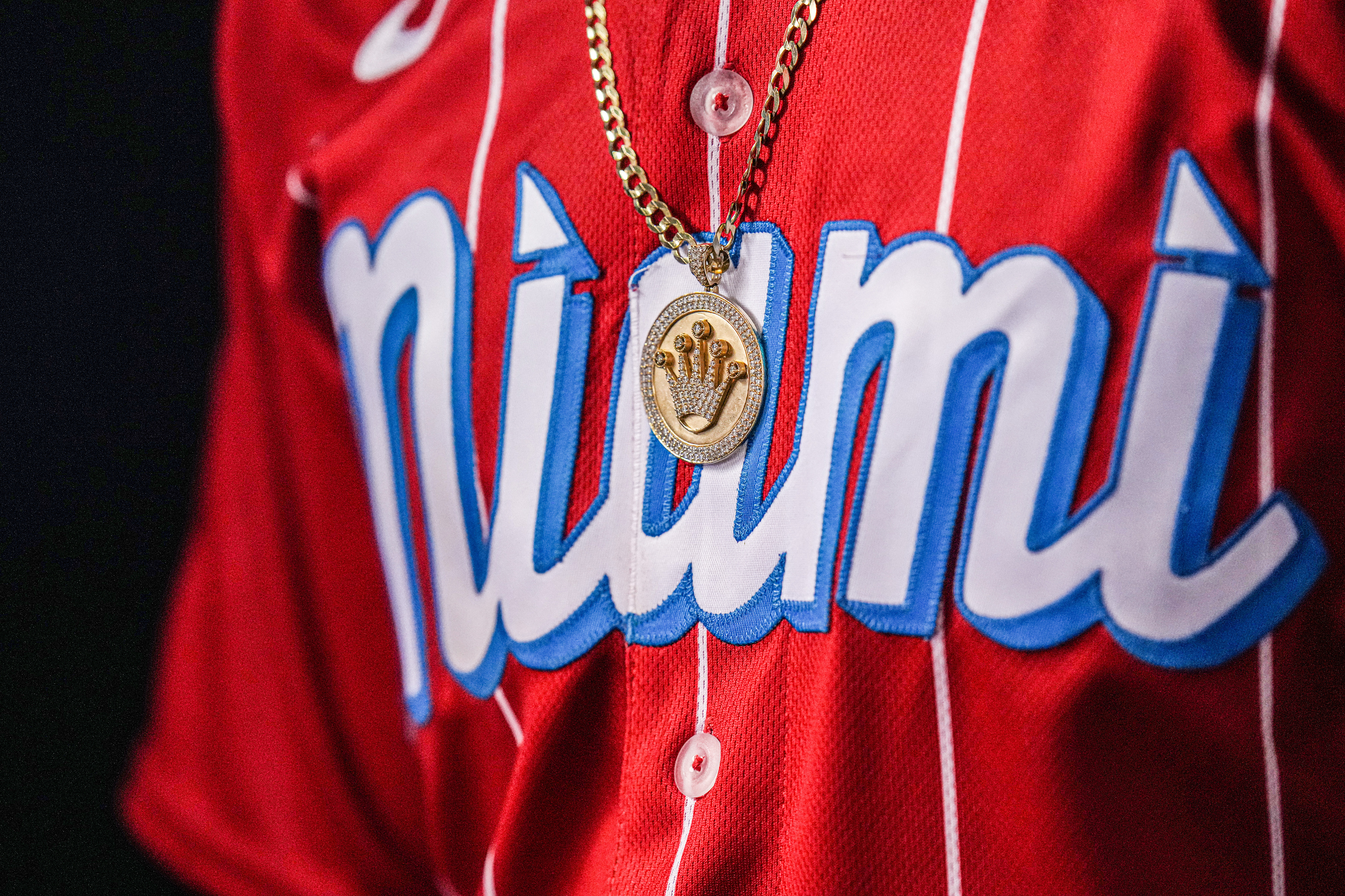 A detailed view of the necklace worn by Bryan De La Cruz #77 of the Miami Marlins in the dugout during the game against the Chicago Cubs at loanDepot park