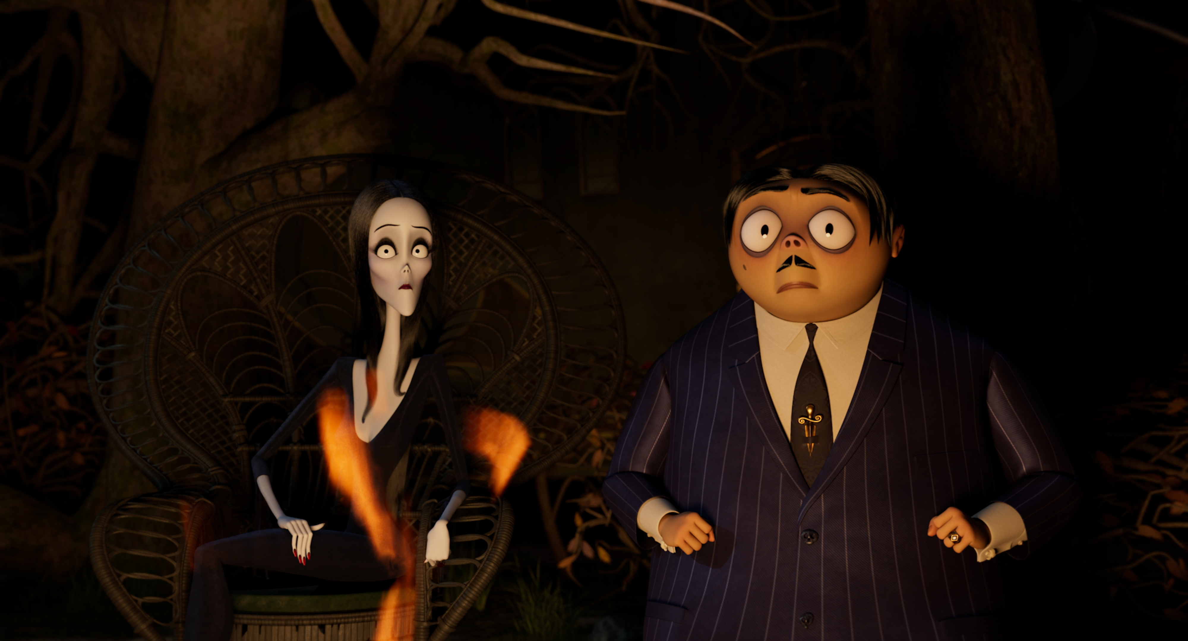 Morticia and Gomez Addams in the dark, staring wide-eyed at something offscreen