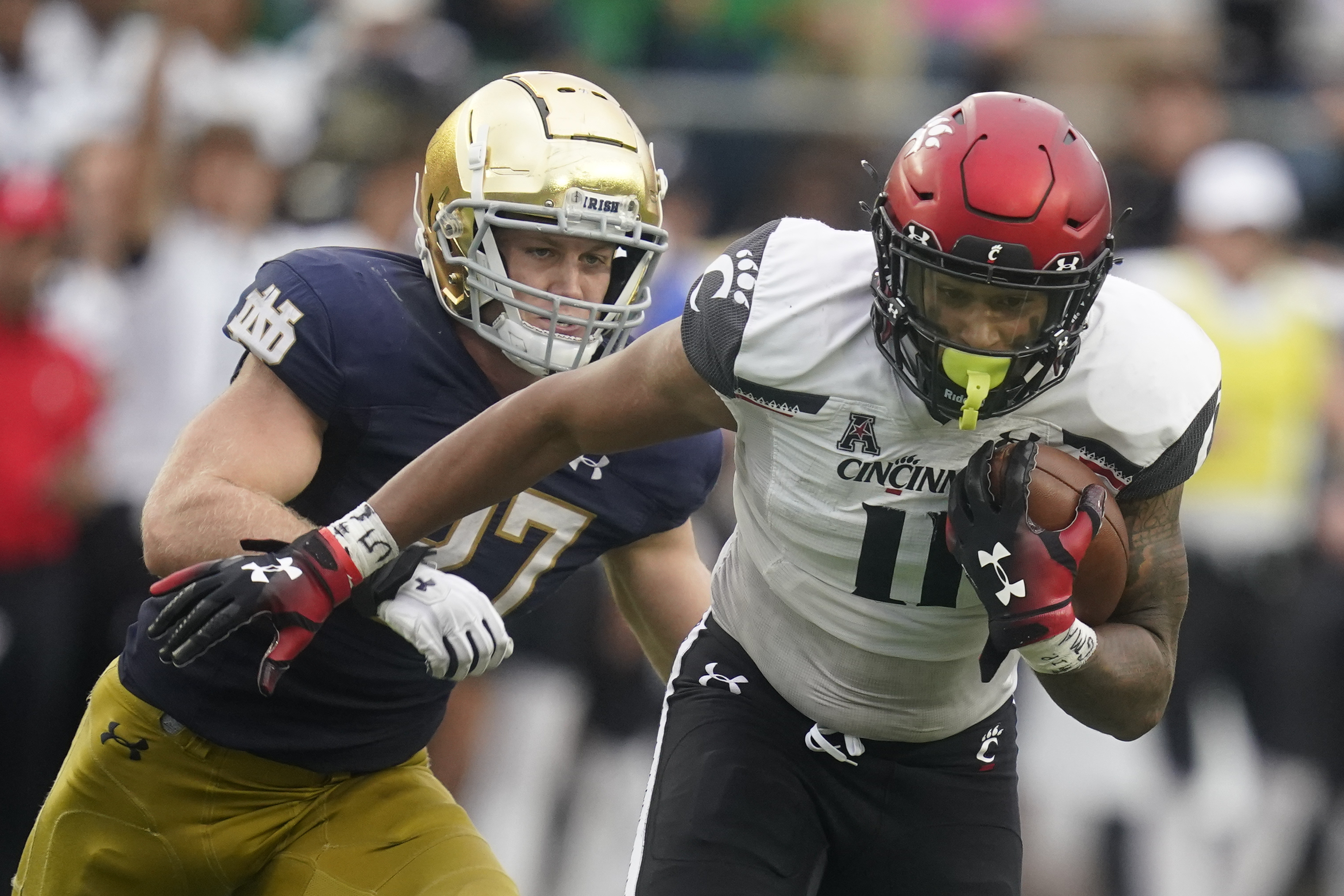Cincinnati's Leonard Taylor (11) is chased by Notre Dame's JD Bertrand (27) during the second half of the Bearcats' win over the Fighting Irish.