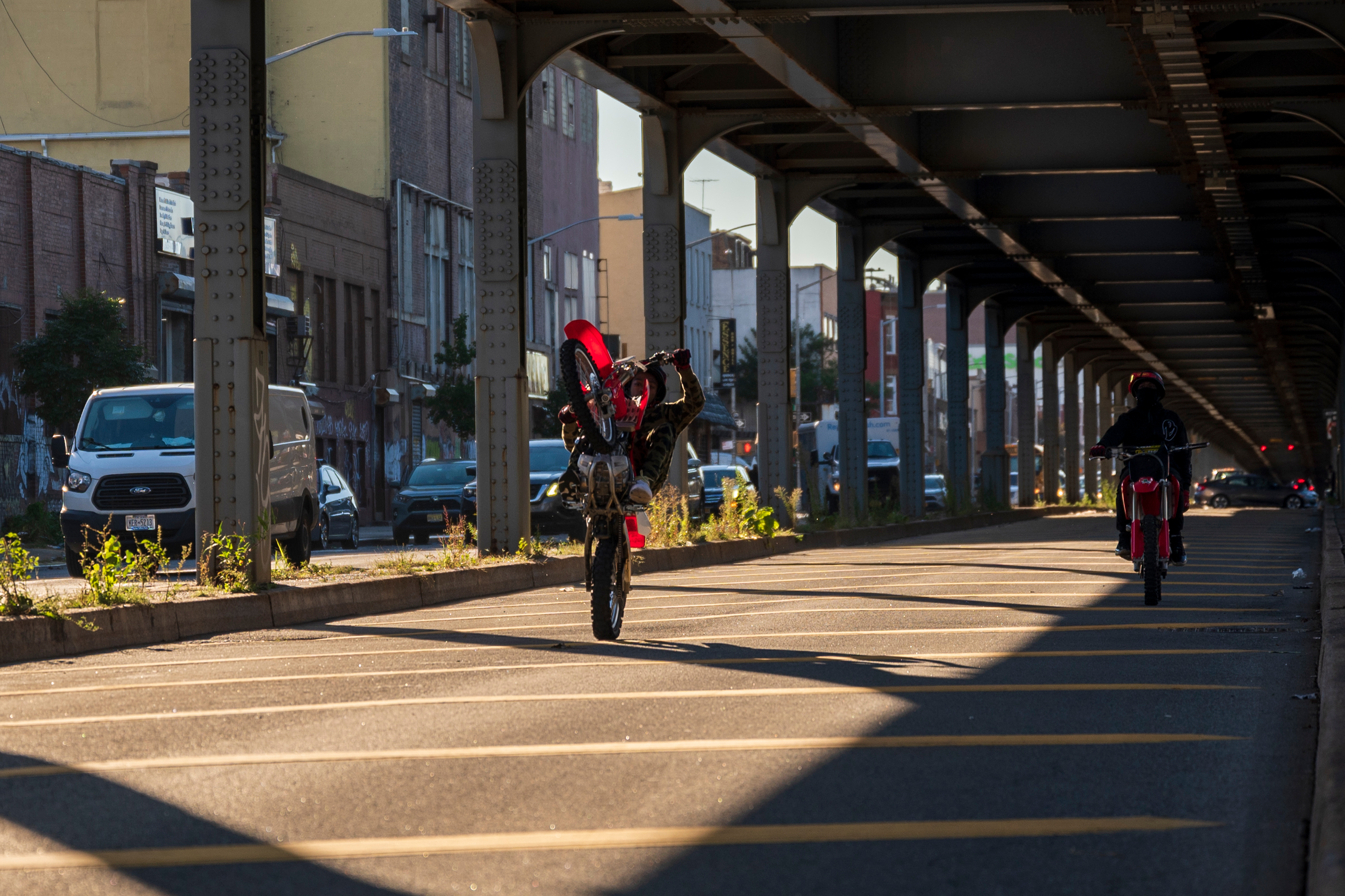 Two dirt bike riders show off their skills beneath the elevated LIRR tracks along Atlantic Avenue in Brooklyn, Sept. 24, 2021.