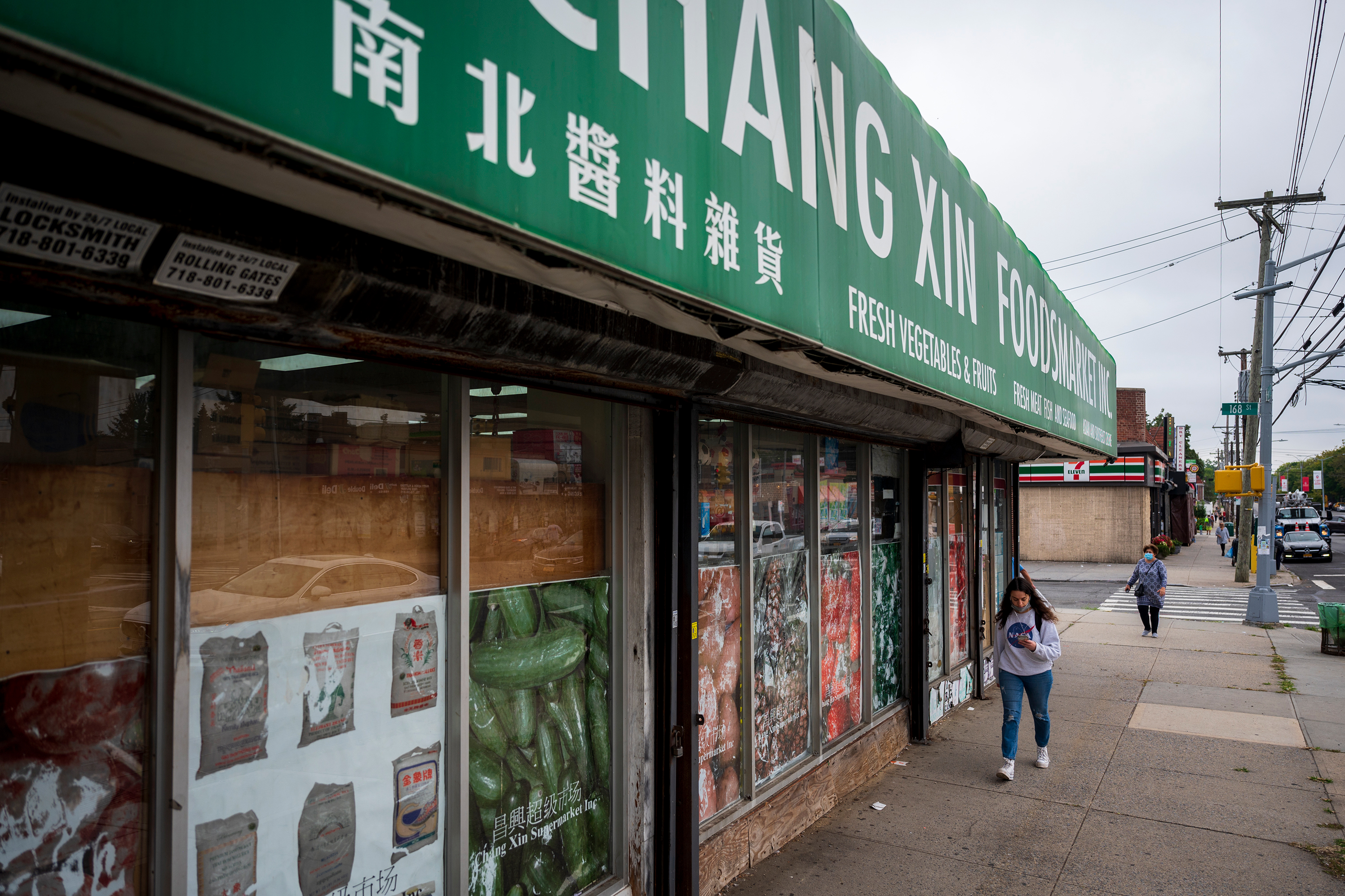 Pedestrians walk past a market at the intersection of Union Turnpike and 168th St in Hillcrest, Queens, Sept. 17, 2021.