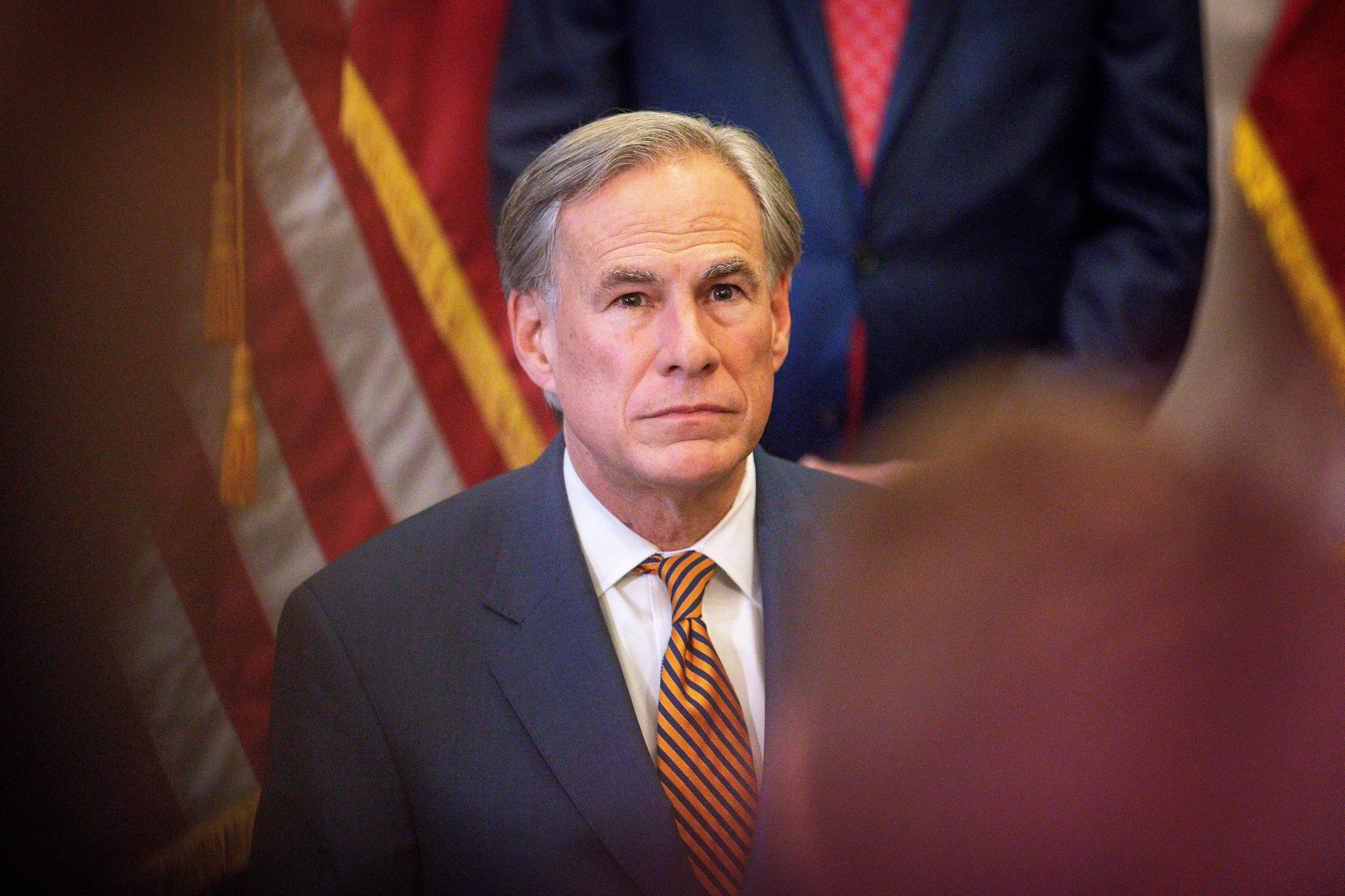 Greg Abbott, wearing a suit and with American flags behind him, is seen facing an audience