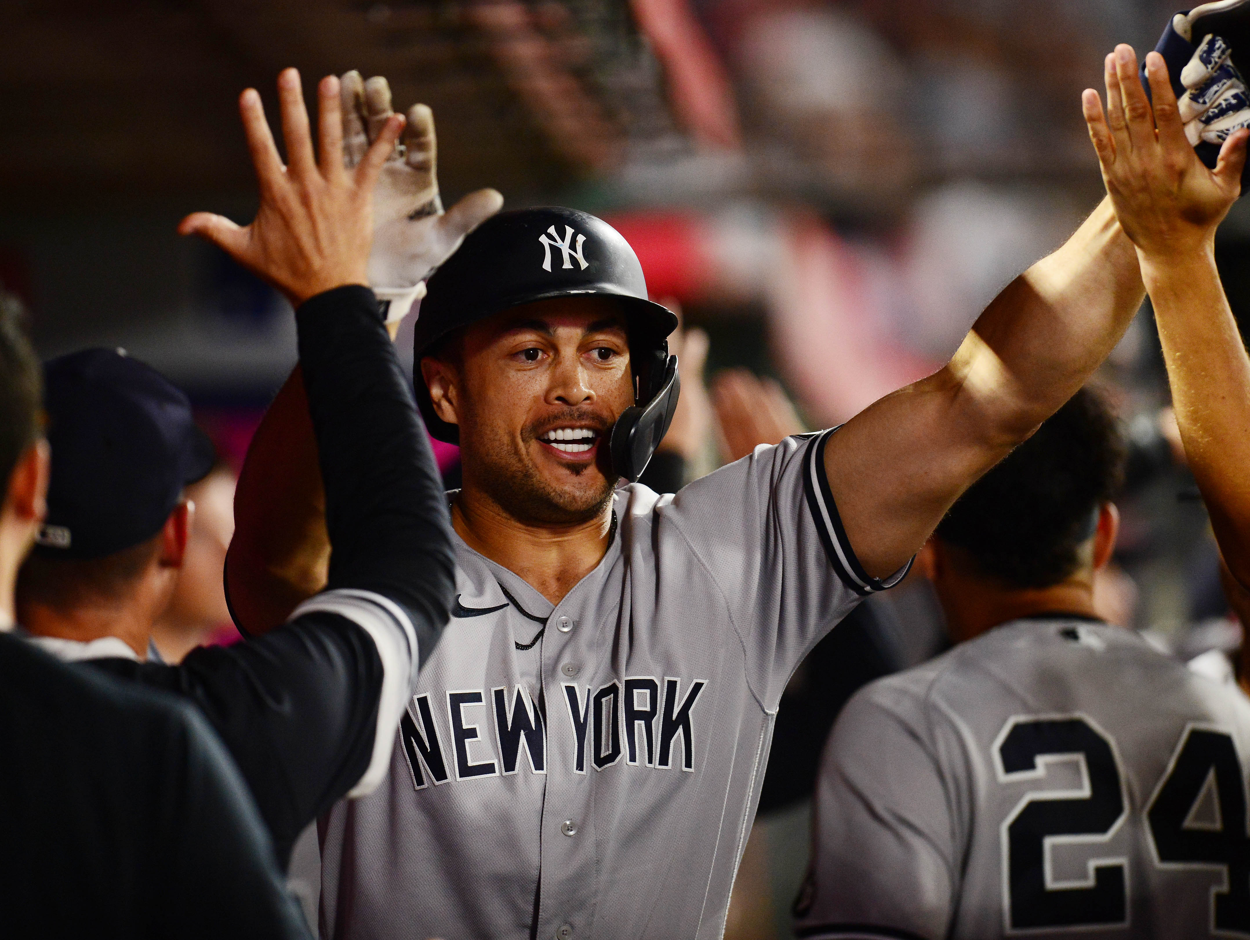 New York Yankees designated hitter Giancarlo Stanton (27) is greeted after hitting a two run home run against the Los Angeles Angels during the seventh inning at Angel Stadium