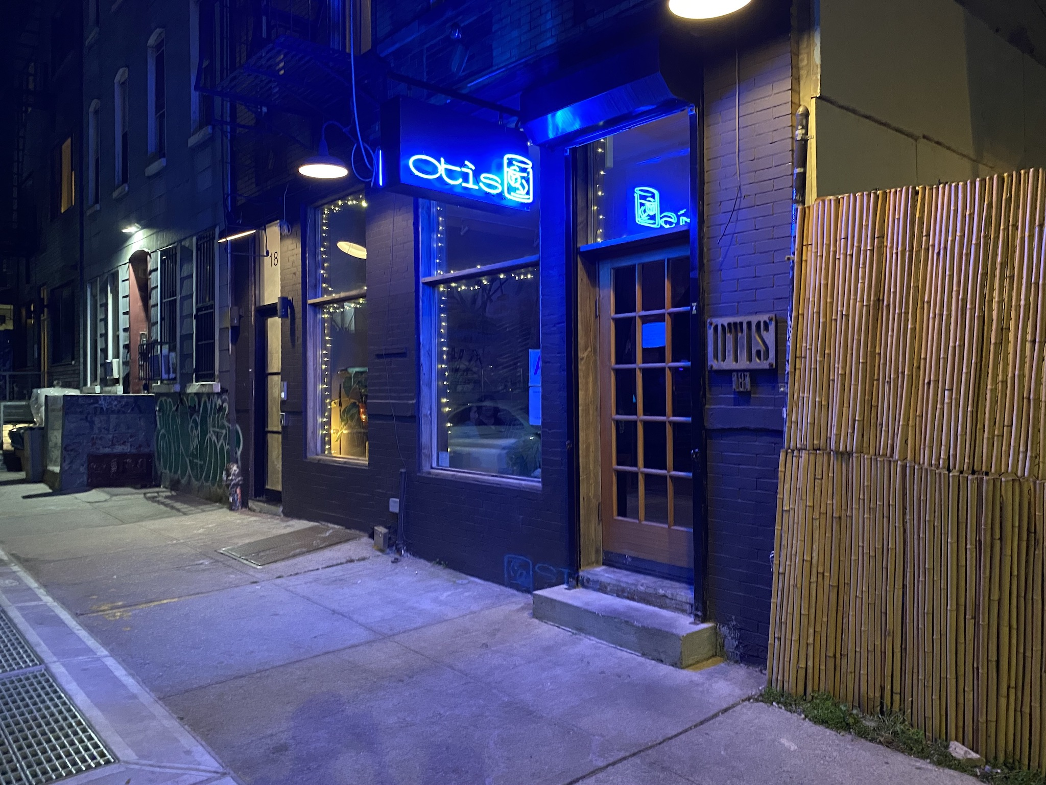 A storefront shot with blue neon lighting hanging above the door.