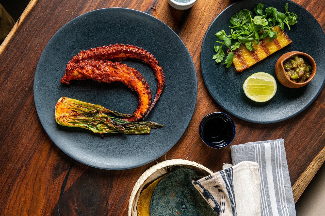 Plates at Maïz64 hold red-tinged roasted octopus al pastor, a grilled piece of pineapple, and blue and yellow tortillas.
