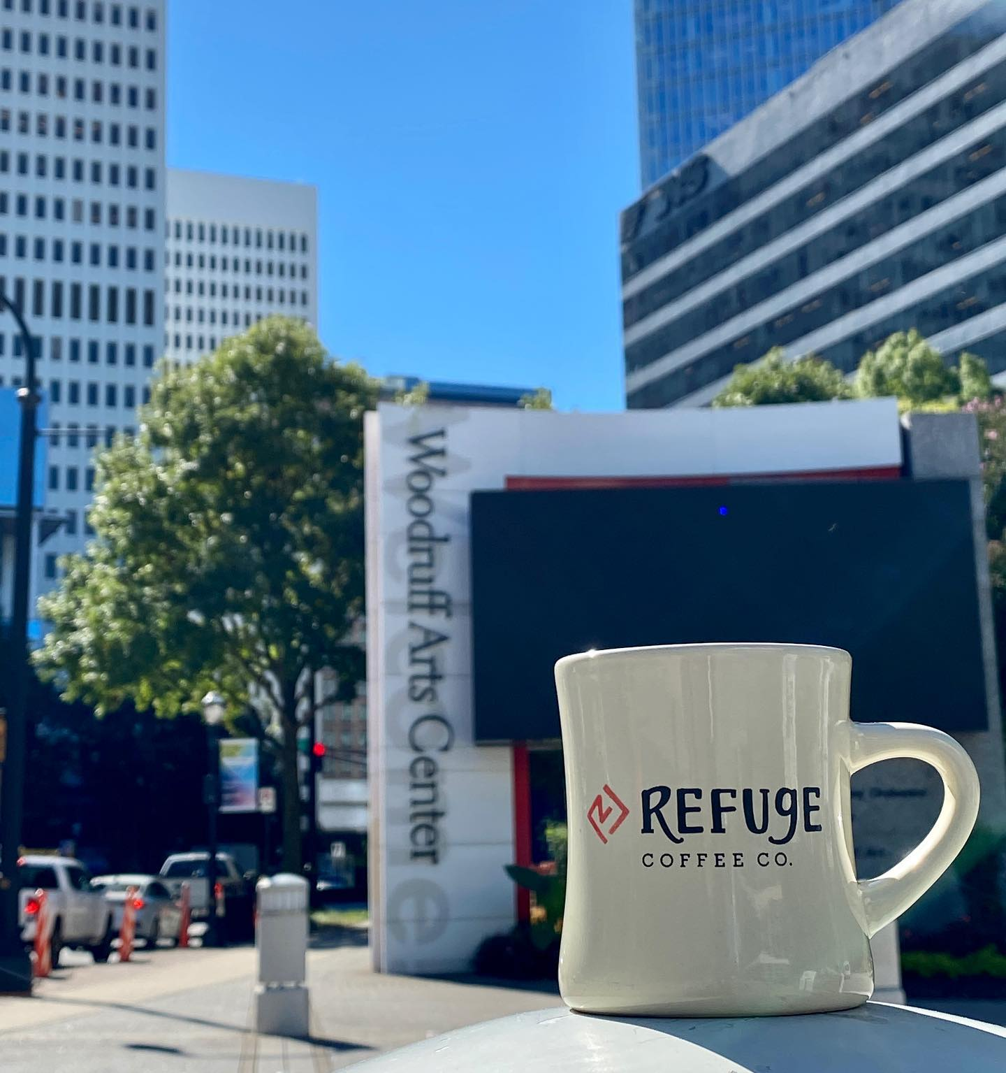 A Refuge Coffee Co. coffee mug sits on a wall which overlooks Woodruff Arts Center in Midtown Atlanta, where the shop will be opening its next location