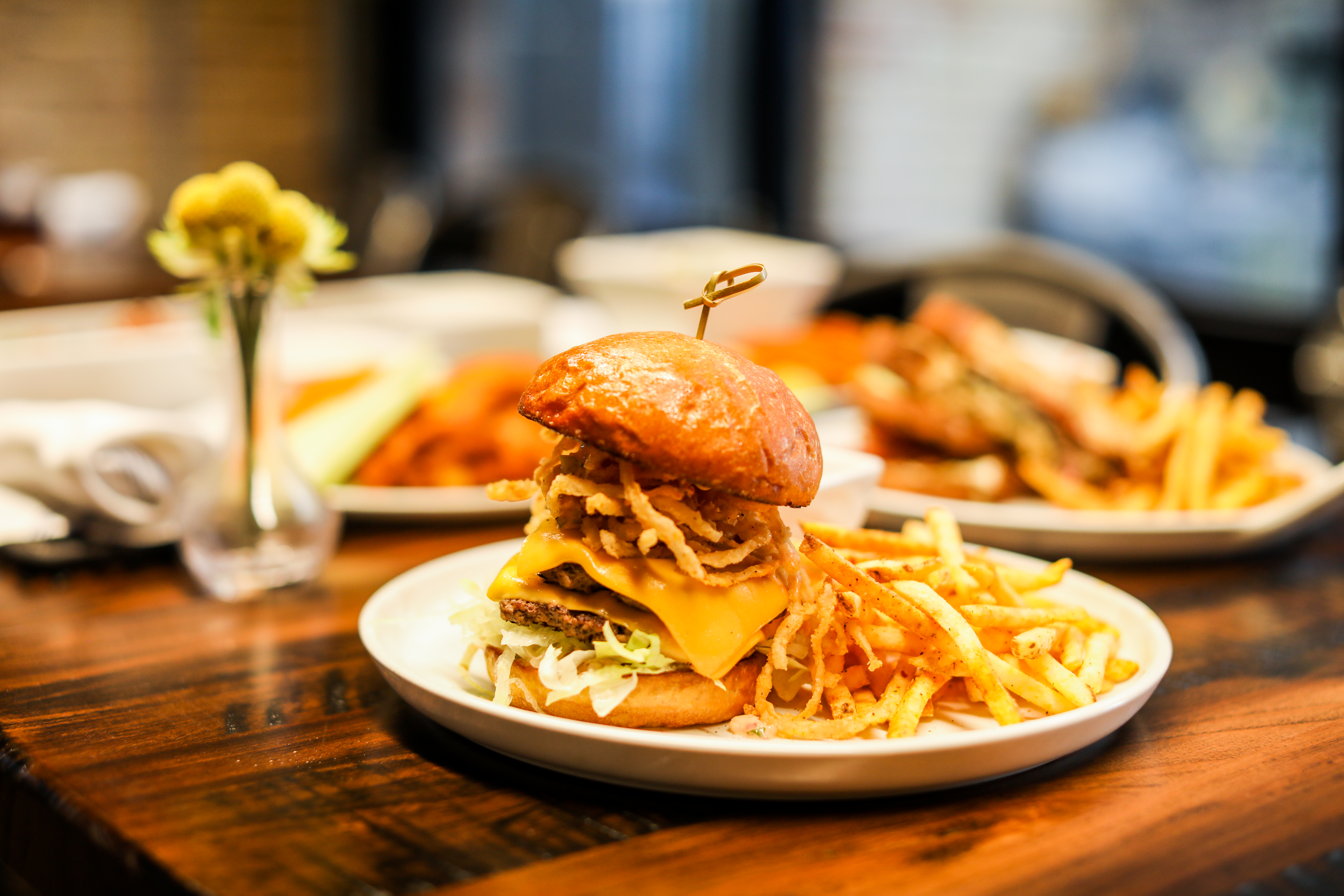 A tall burger with onion rings inside and fries on the plate on a table with a flower