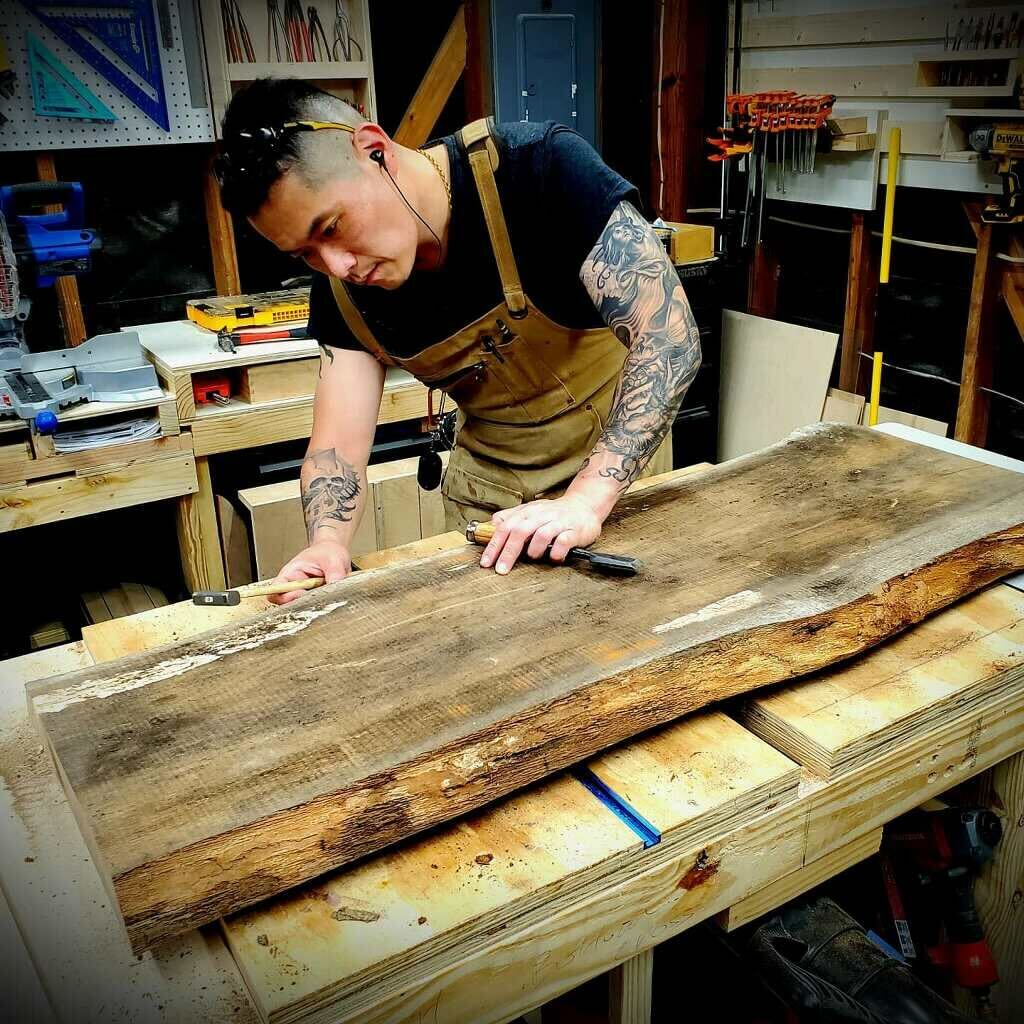 a man with tattoos and wearing an apron leans over a plank of wood in a woodworking shop