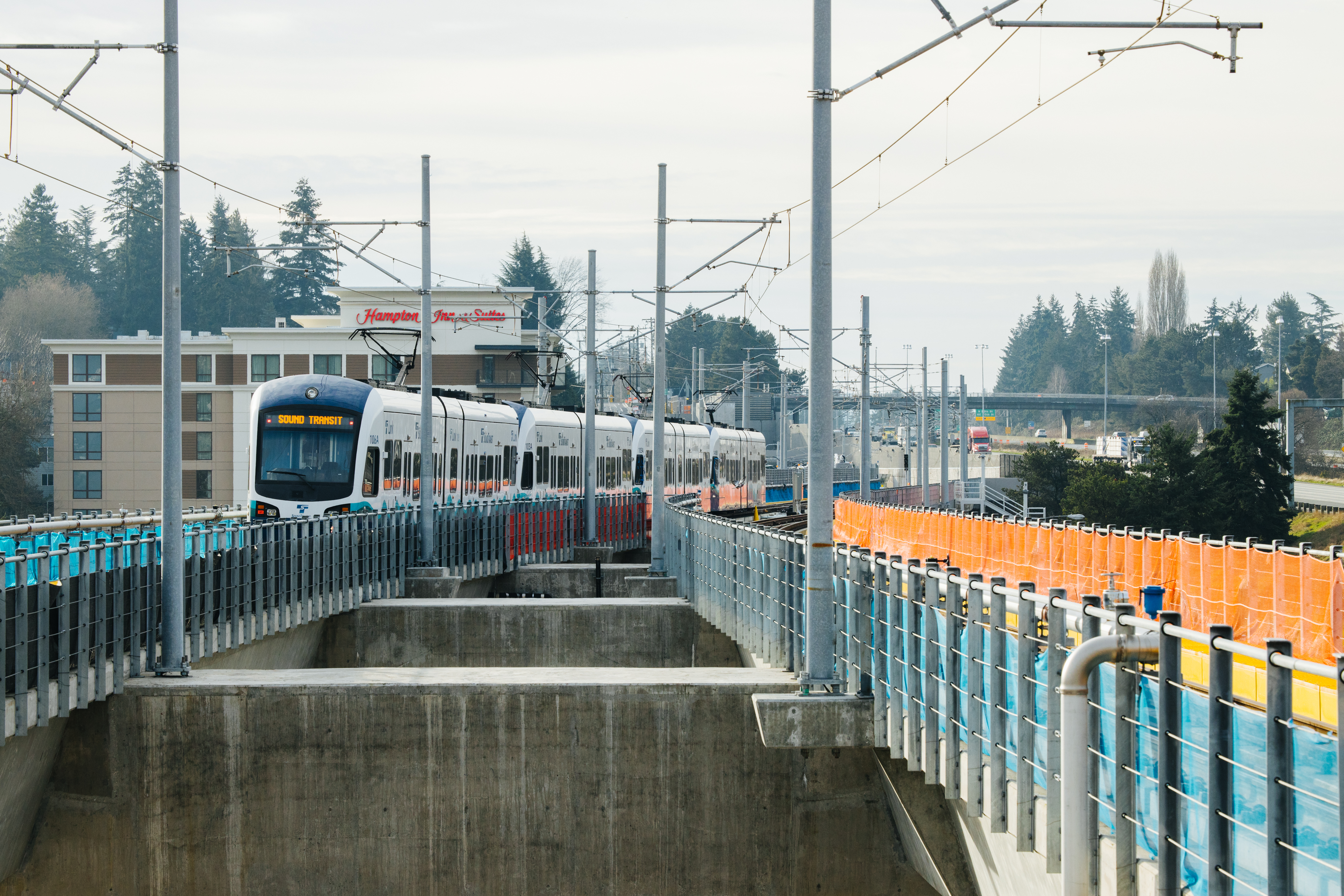 A white and black Link Light Rail train comes towards the viewer.