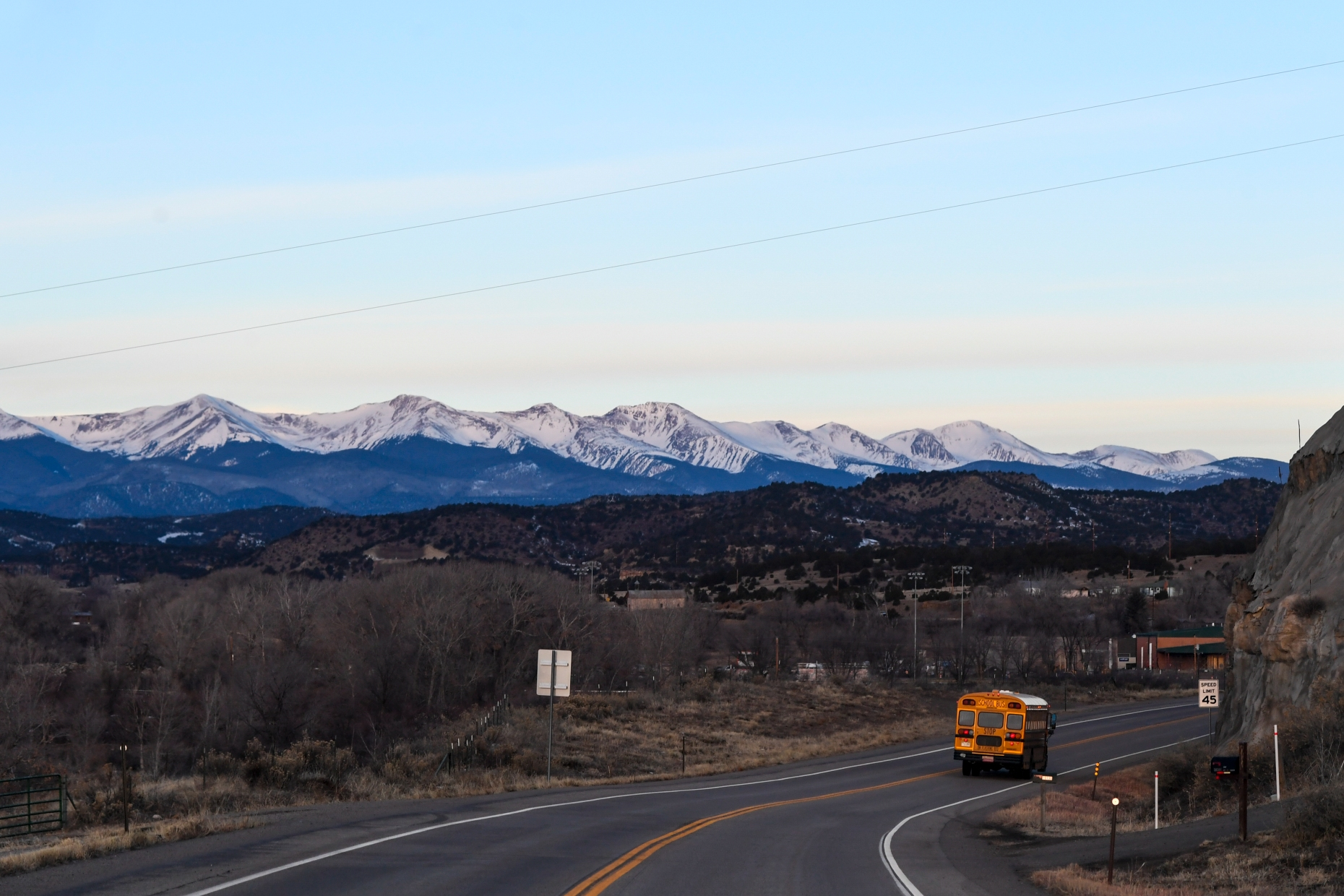 A yellow school bus drives around a curve in the highway with a view of snow-capped mountains and blue skies in the background.